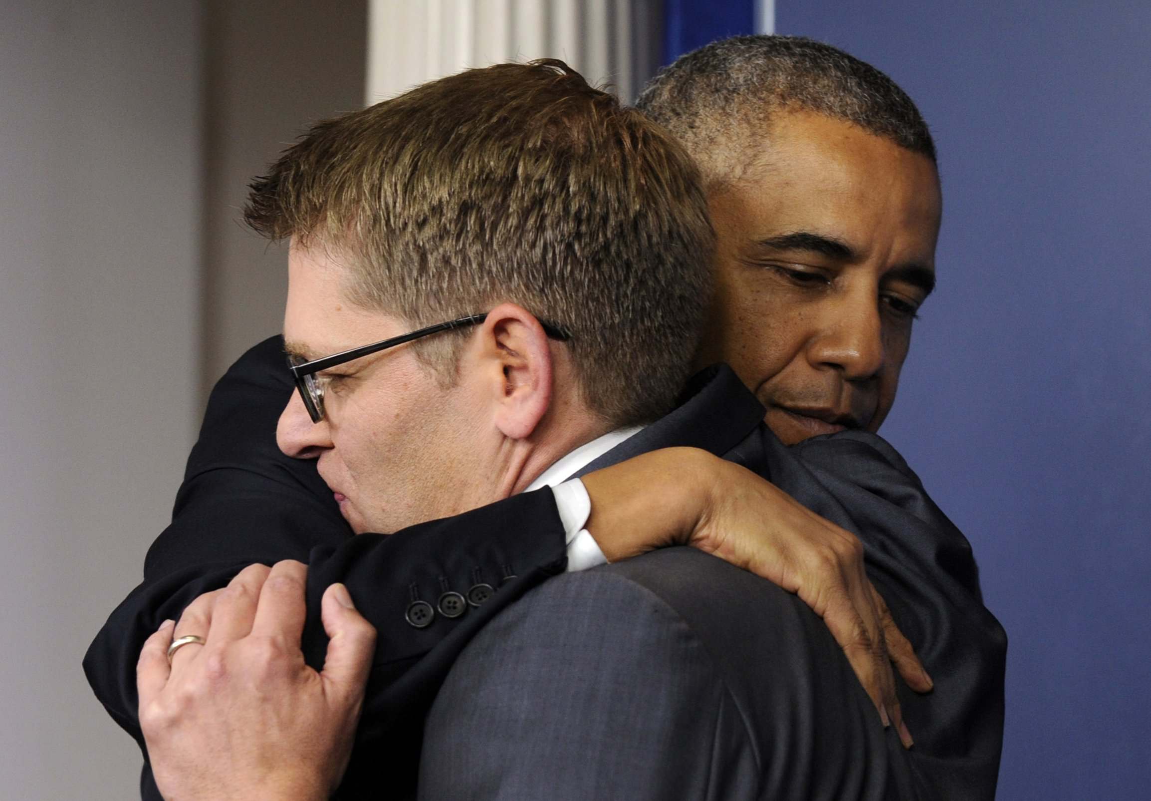 President Barack Obama gives White House press secretary Jay Carney a hug after announcing that Carney will step down later next month, during a surprise visit to the Brady Press Briefing Room of the White House on May 30, 2014 in Washington.