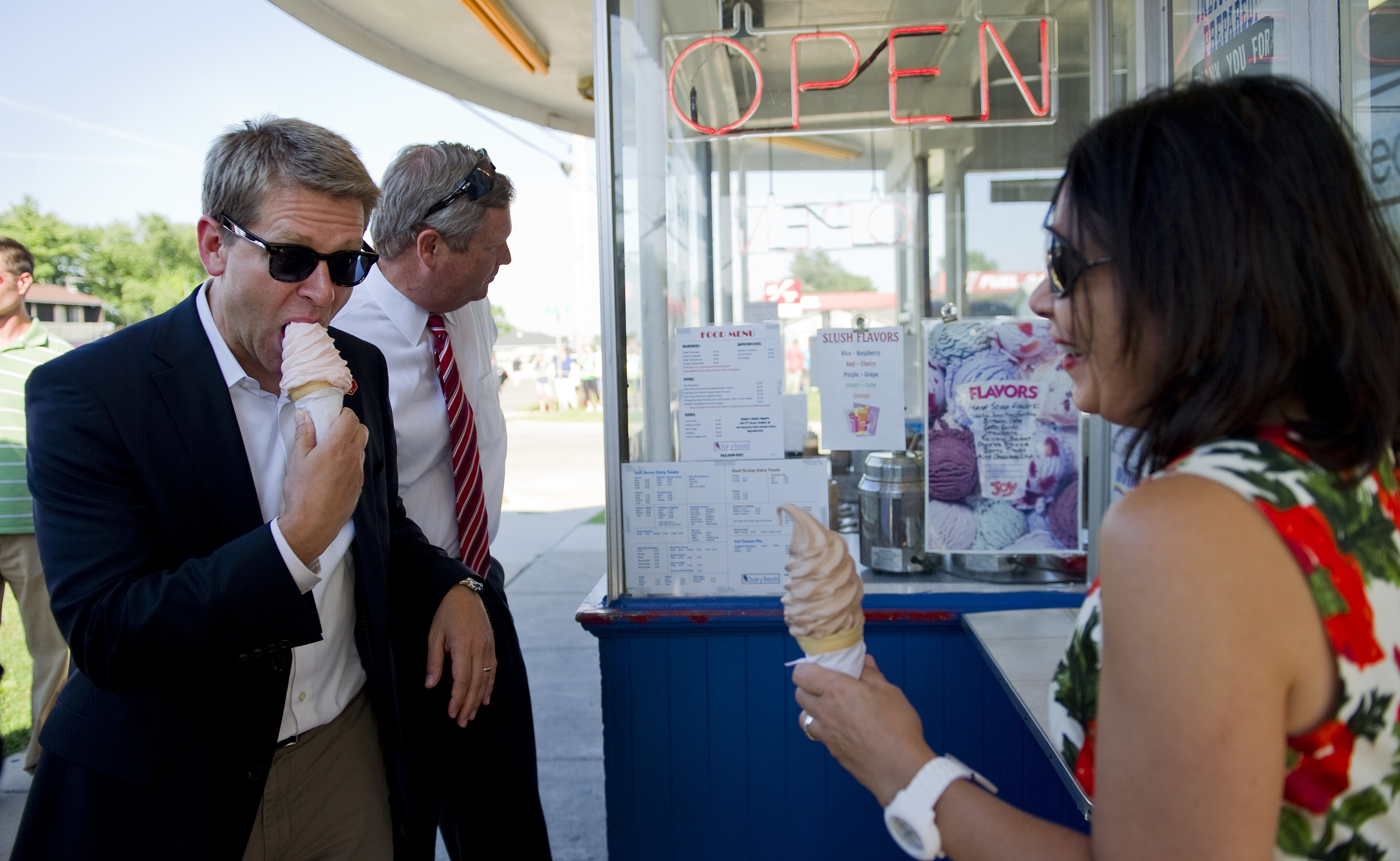 White House Press Secretary Jay Carney (L), US Agriculture Secretary Tom Vilsack (C) and Deputy White House chief of Staff Nancy DeParle (R) get ice cream cones as US President Barack Obama visits DeWitt Dairy Treats in Dewitt, Iowa, August 16, 2011.