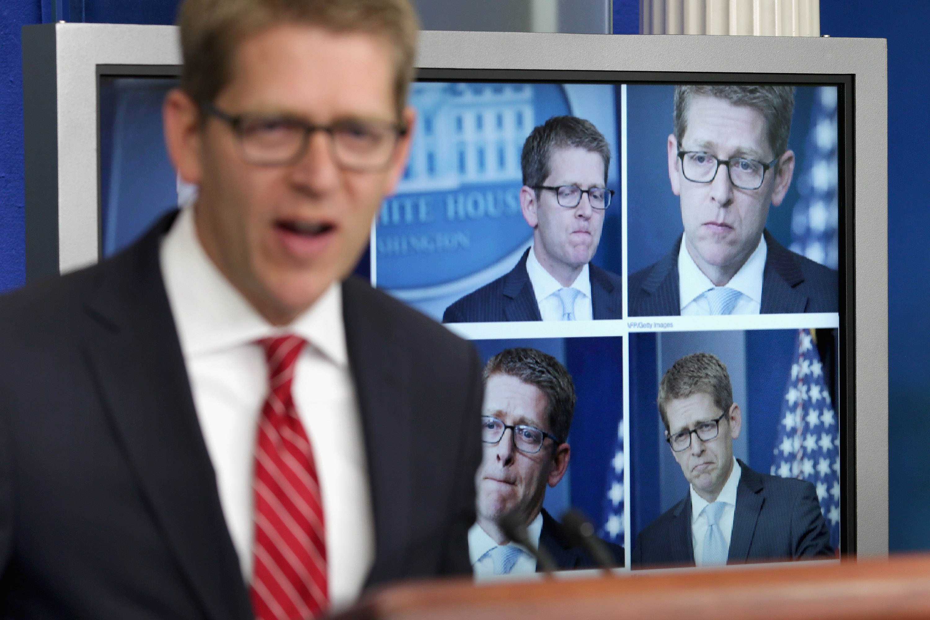 White House Press Secretary Jay Carney displays photographs of himself from Tuesday's briefing before taking questions from reporters in the Brady Press Briefing Room at the White House on May 15, 2013 in Washington.