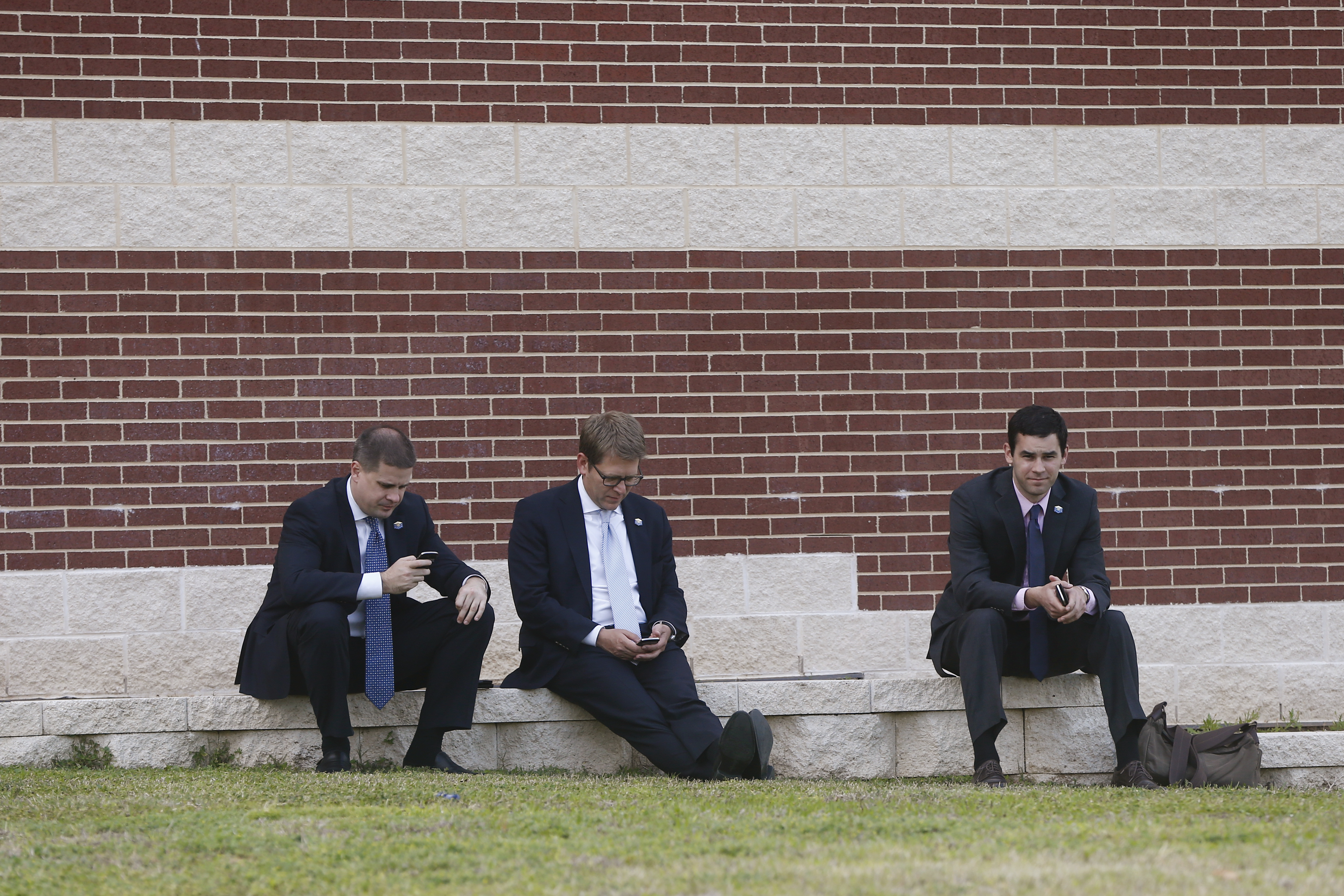 White House Press Secretary Jay Carney, center, senior adviser Dan Pfeiffer, left, and speechwriter Kyle O'Connor wait outside as President Barack Obama and first lady Michelle Obama meet with families of firefighters killed in the West Texas, fertilizer plant explosion after a memorial at Baylor University in Waco,Texas on April 25, 2013.