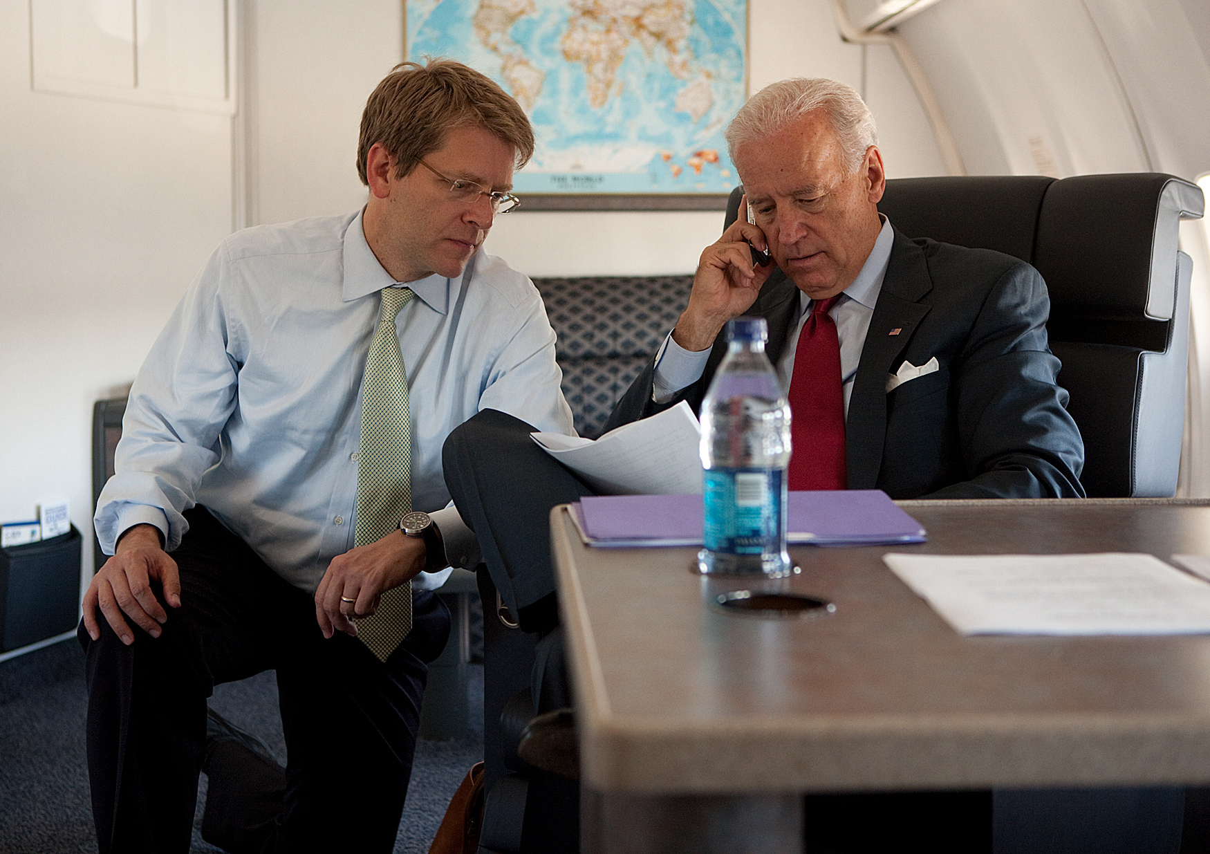 In this image released by the White House, Vice President Joe Biden works with Communications Director Jay Carney on Air Force Two en route to Atherton, Calif., July 8, 2010.