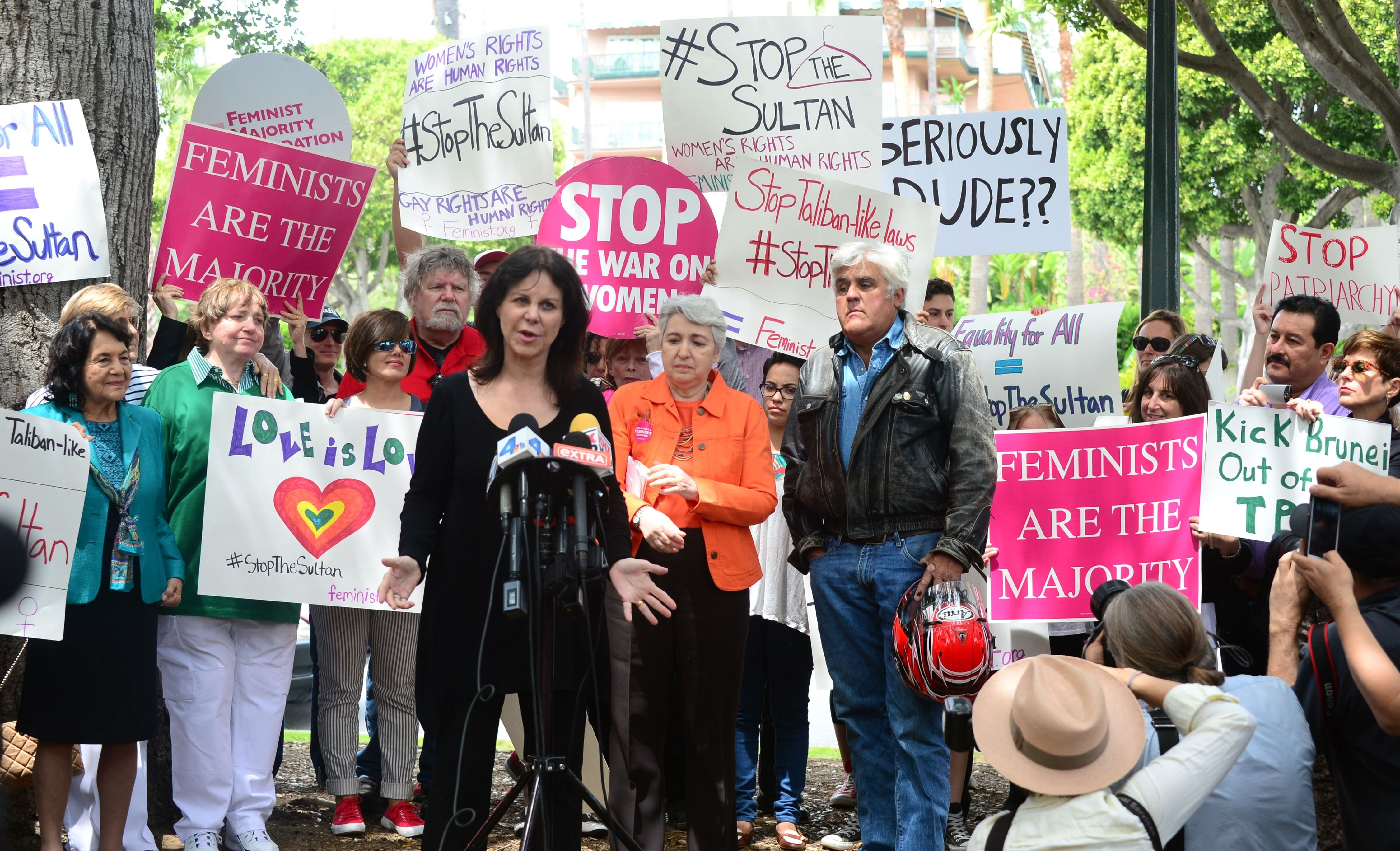 Jay Leno watches as his wife Mavis speaks to supporters of women's rights and LGBT groups at a protest across from the Beverly Hills Hotel, owned by the Sultan of Brunei, on May 5, 2014 in Beverly Hills, Calif.