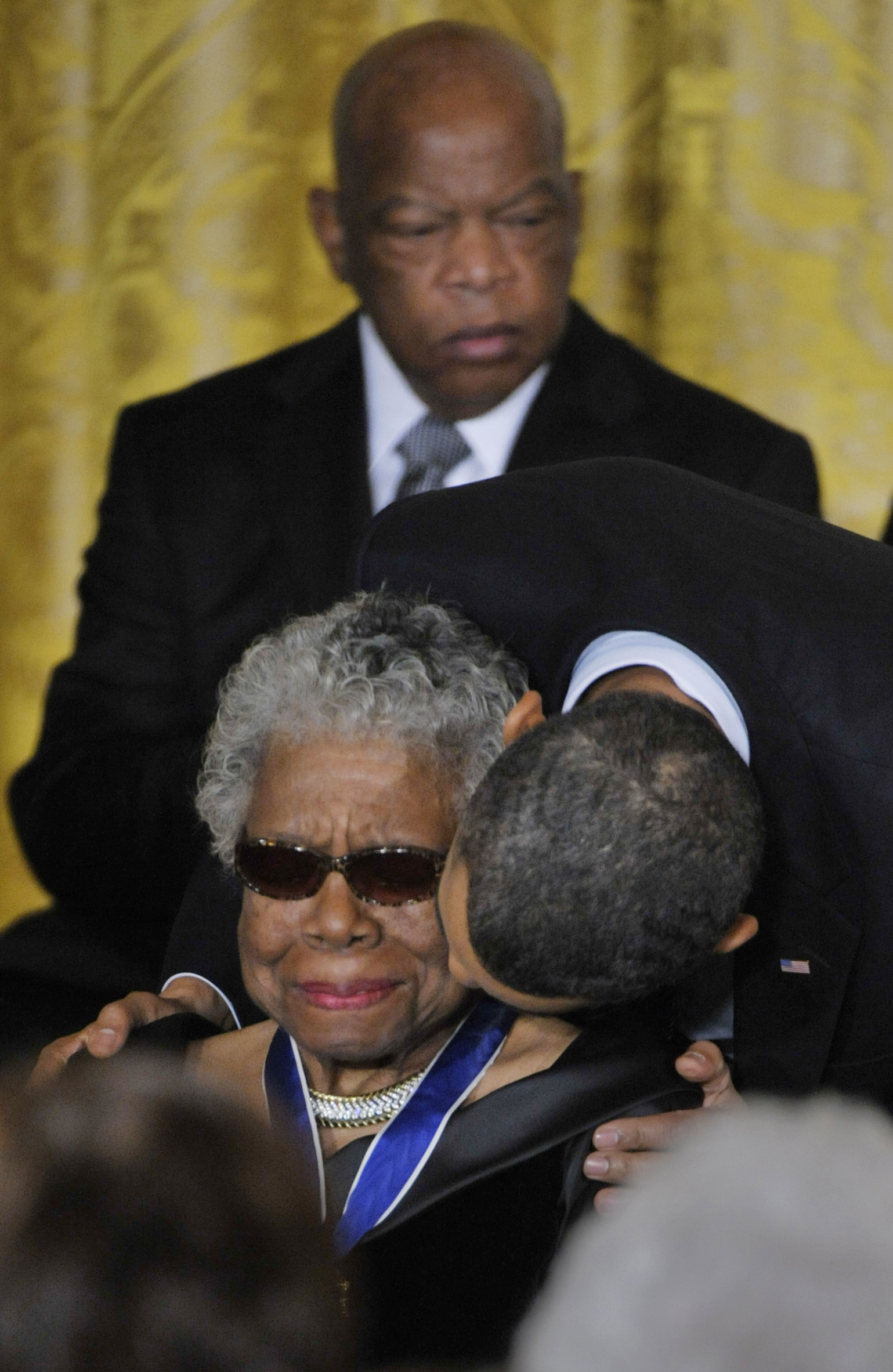 President Obama awards Poet Maya Angelou with the Medal of Freedom as well as a kiss on her cheek, with Medal of Freedom recipient Congressman John Lewis (D-GA) at the White House on February 15, 2011 in Washington.