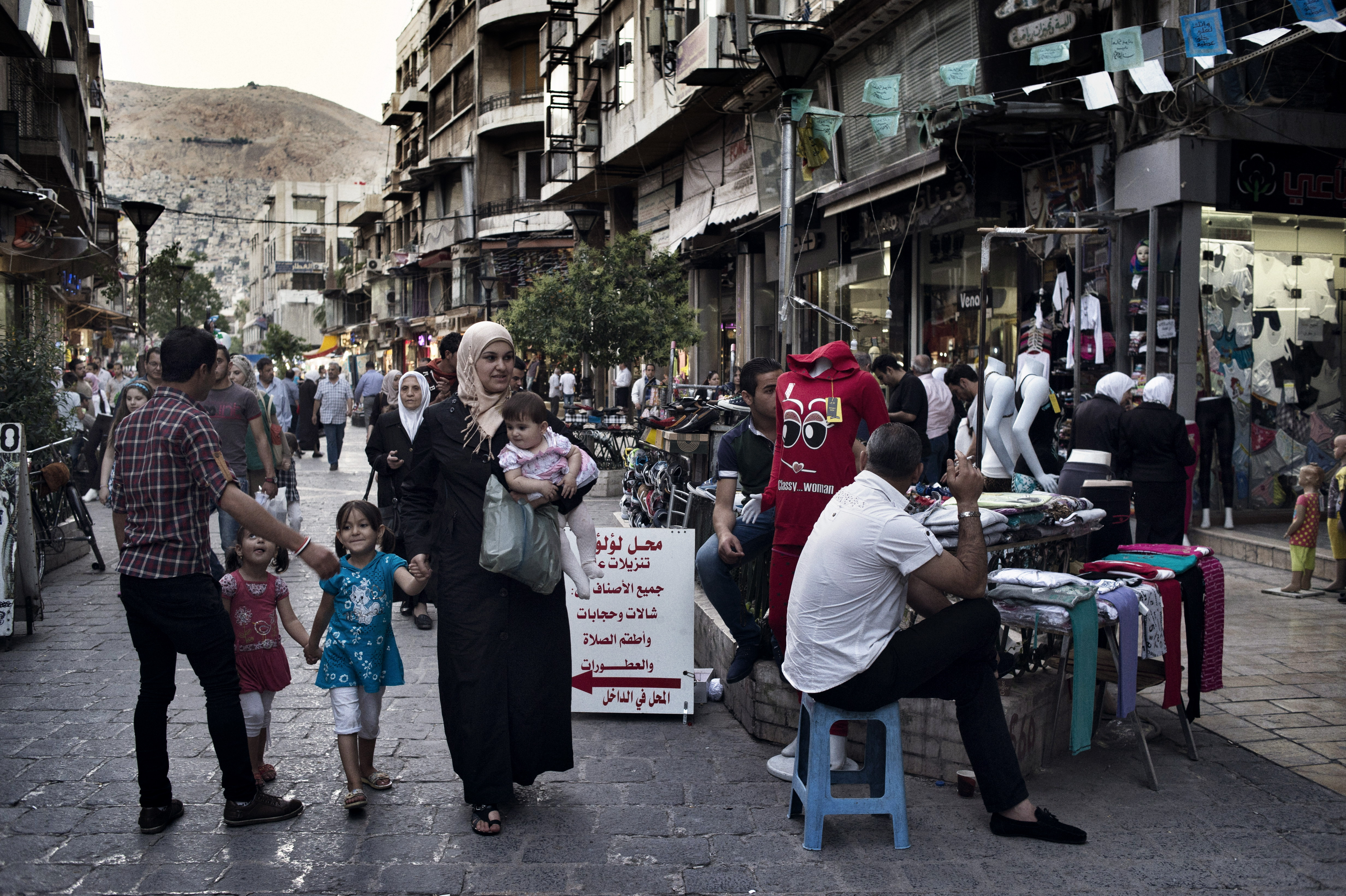 A family walks down a street in Damascus on May 14, 2014.