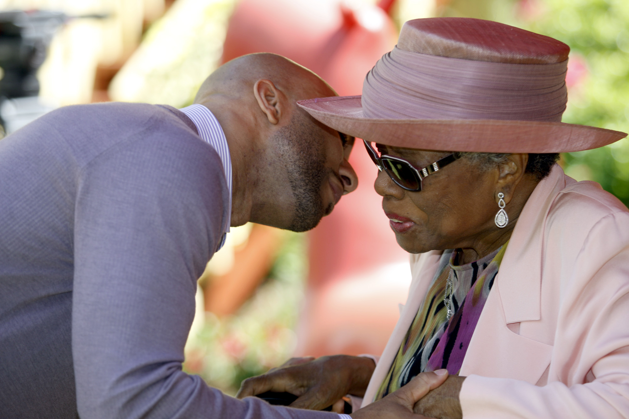 Common greets Maya Angelou at a garden party at Angelou's home in 2010.