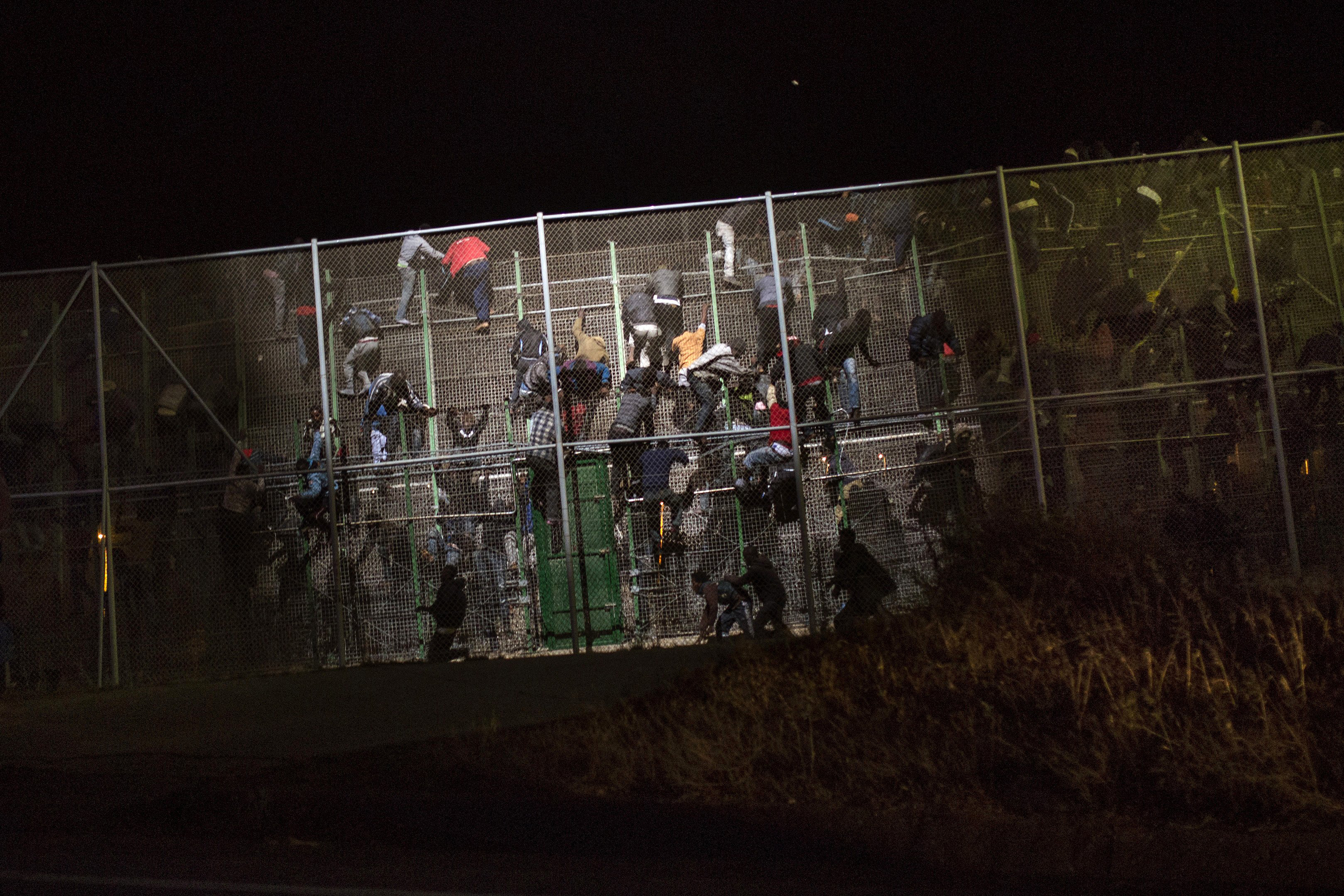 Sub-Saharan migrants scale a metallic fence that divides Morocco and the Spanish enclave of Melilla, early on May 28,  2014.
