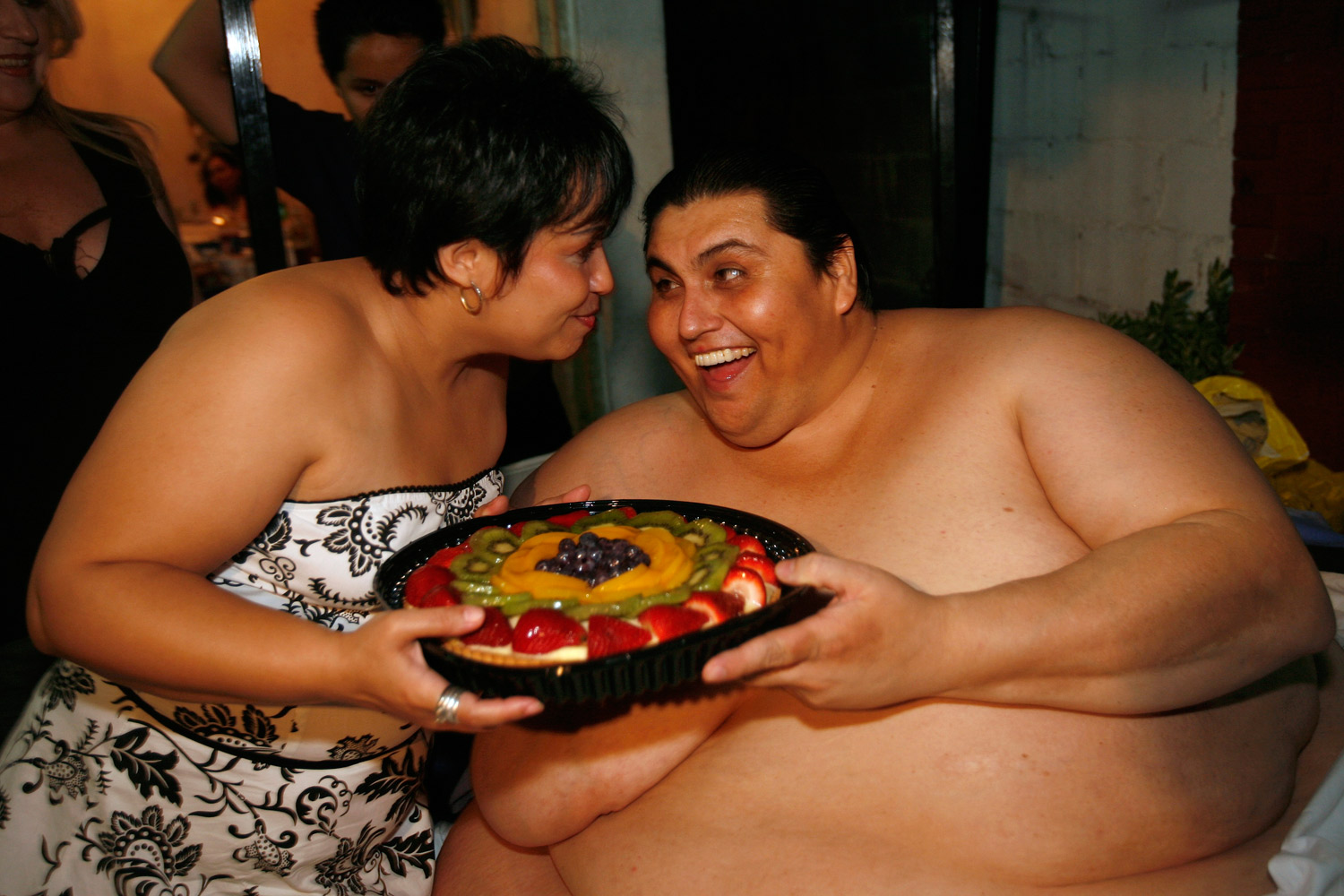 Manuel Uribe jokes as he holds a fruit cake with his girlfriend Claudia Solis outside his house in the suburb of San Nicolas de los Garza in the northern city of Monterrey, Mexico, June 11, 2008.