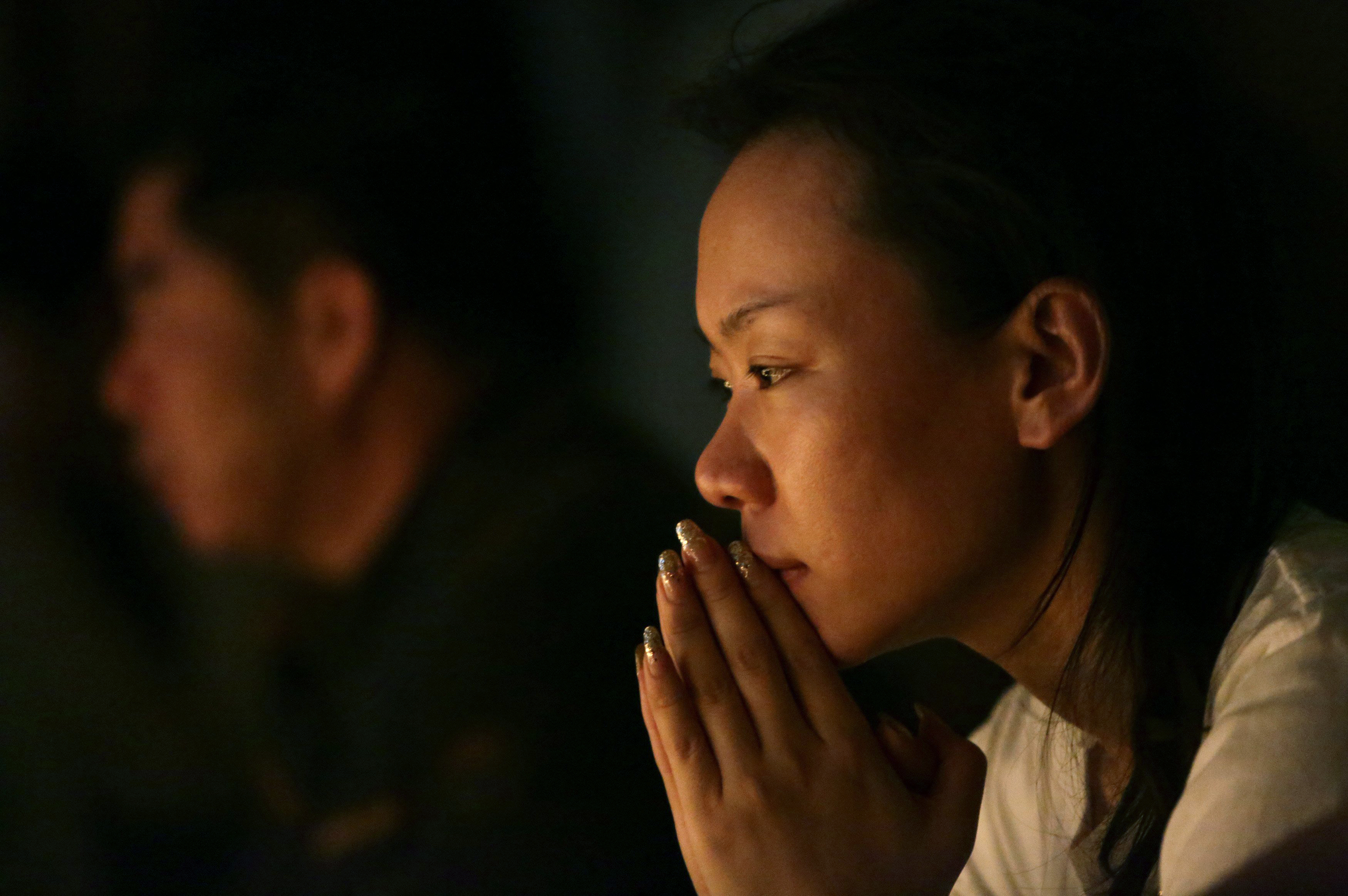 Family members pray during a candlelight vigil for passengers onboard the missing Malaysia Airlines Flight MH370 in the early morning, at Lido Hotel, in Beijing on April 8, 2014.