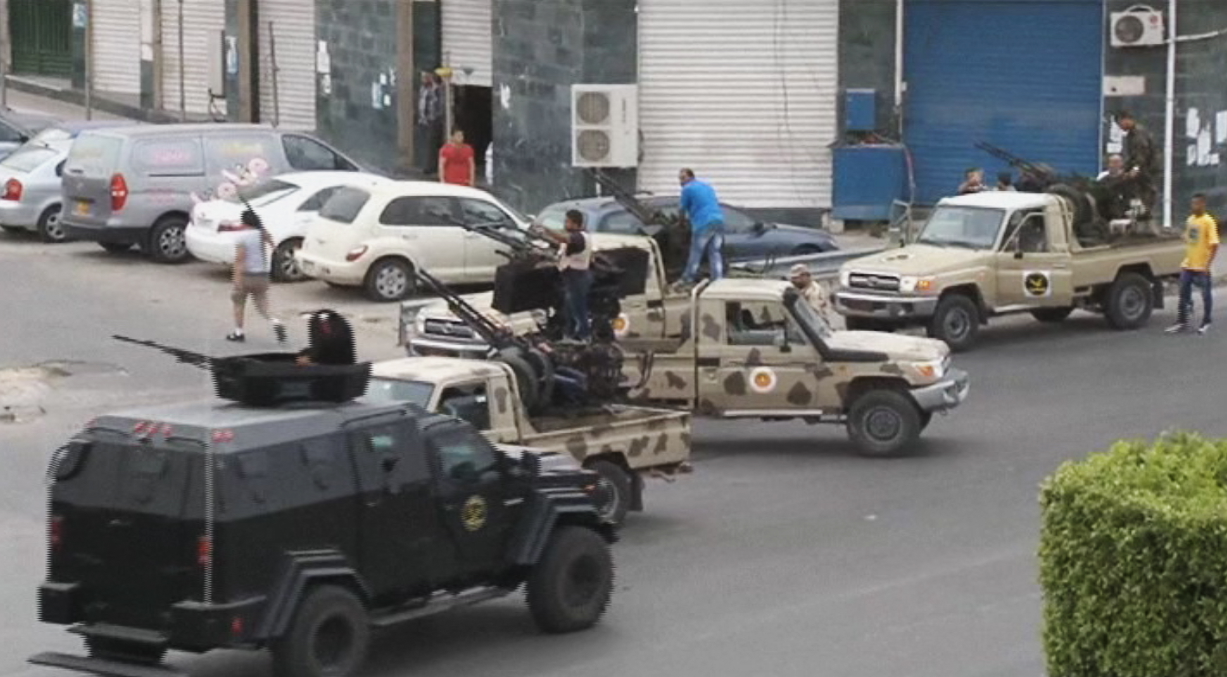 Joint security forces on vehicles with heavy artillery stand guard on the entrance road to Libya's parliament area after troops of General Khalifa Hifter targeted Islamist lawmakers and officials at the parliament in Tripoli on Sunday, May 18, 2014.