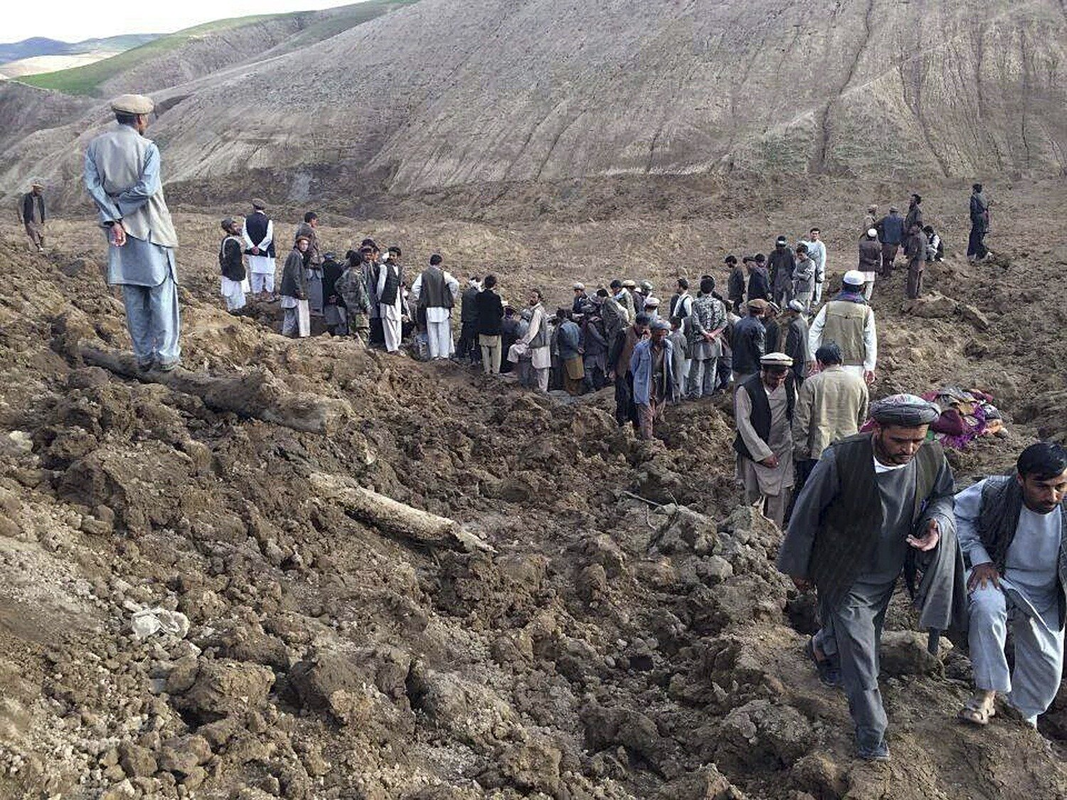 Afghan villagers gather at the site of a landslide at the Argo district in Badakhshan province, May 2, 2014.