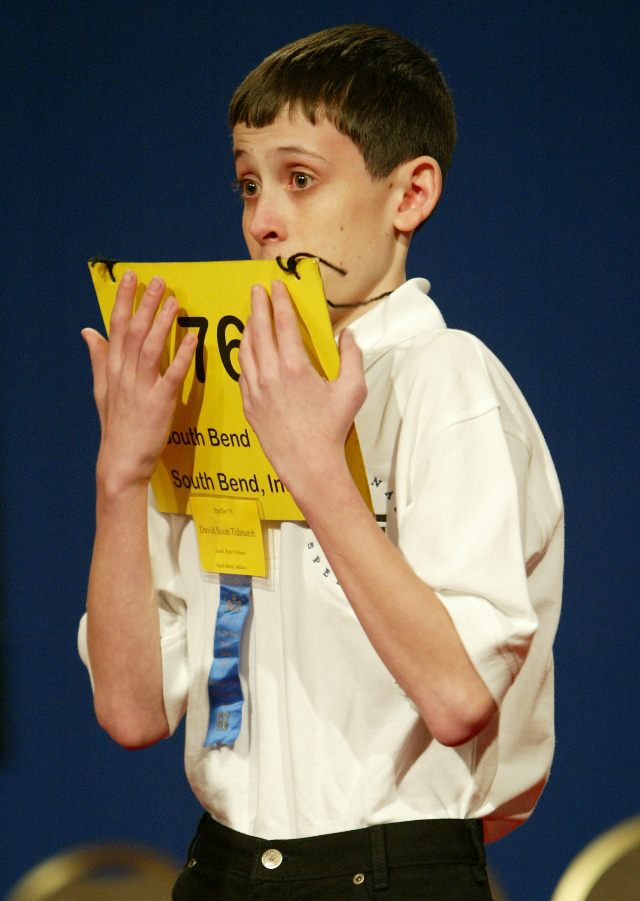 "David Tidmarsh, 14, of South Bend, Indi. peers over his placard after spelling the word ""gaminerie"" correctly to advance to round 15 during the National Spelling Bee on June 3, 2004 in Washington."