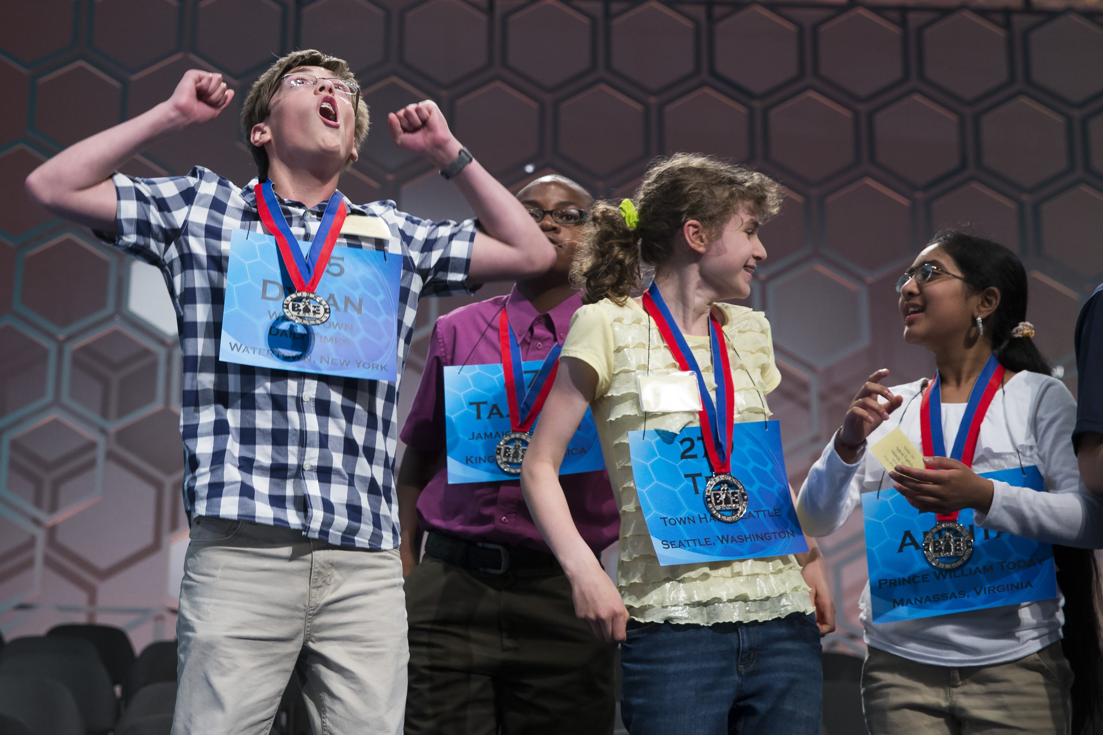 From left, Dylan O'Connor of Alexandria Bay, N.Y., Tajaun Gibbison of Mandeville, Jamaica, Téa Freedman-Susskind of Redmond, Wash., and Ankita Vadiala of Manassas, Va., celebrate after they qualified for the semifinal round of the National Spelling Bee on May 28, 2014 in Oxon Hill, Md.