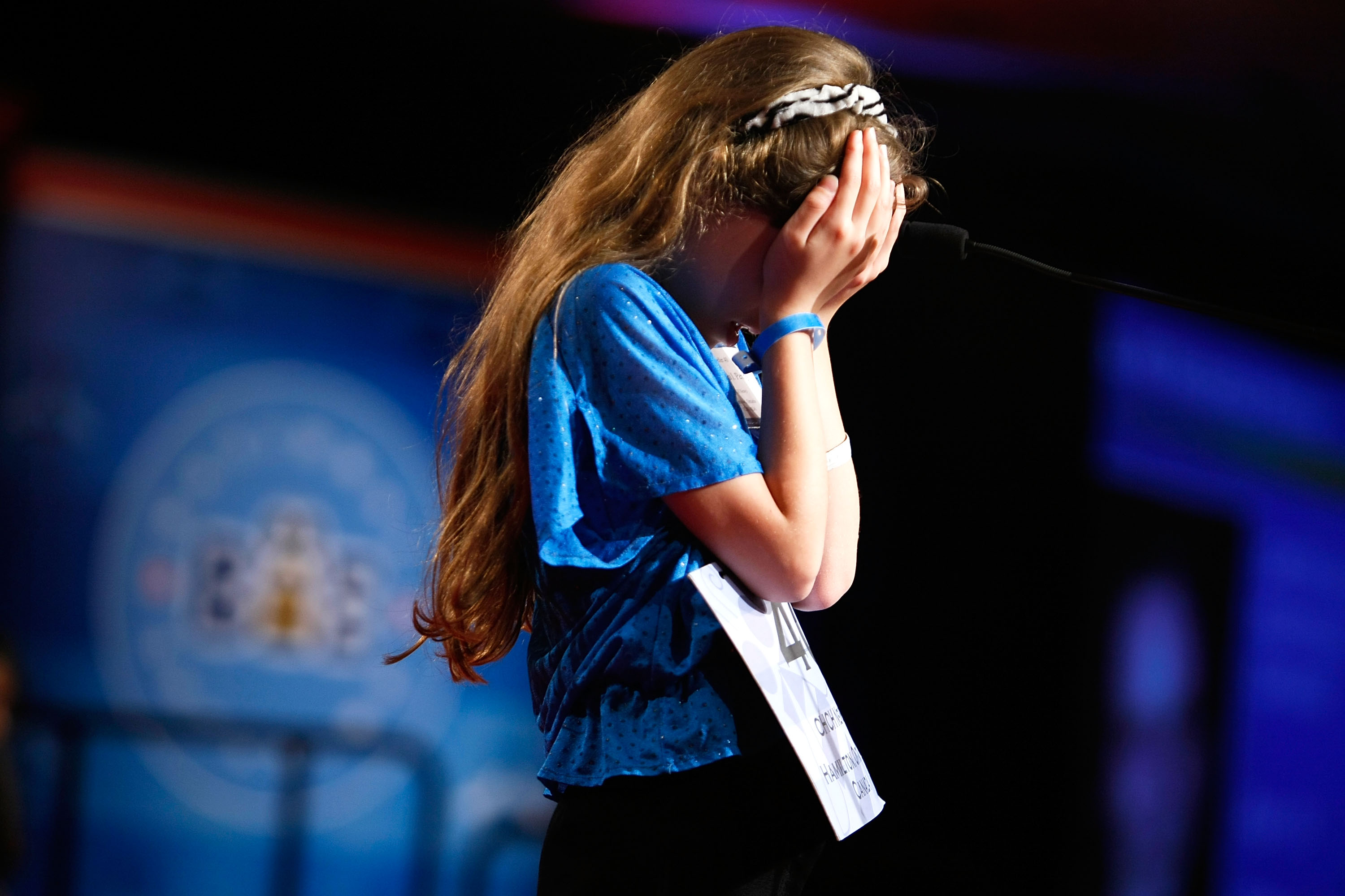 "Veronica Penny of Hamilton, Ontario, Canada, covers up her face as she tries to spell the word ""clary"" during round four of the Scripps National Spelling Bee competition on May 28, 2009 in Washington."