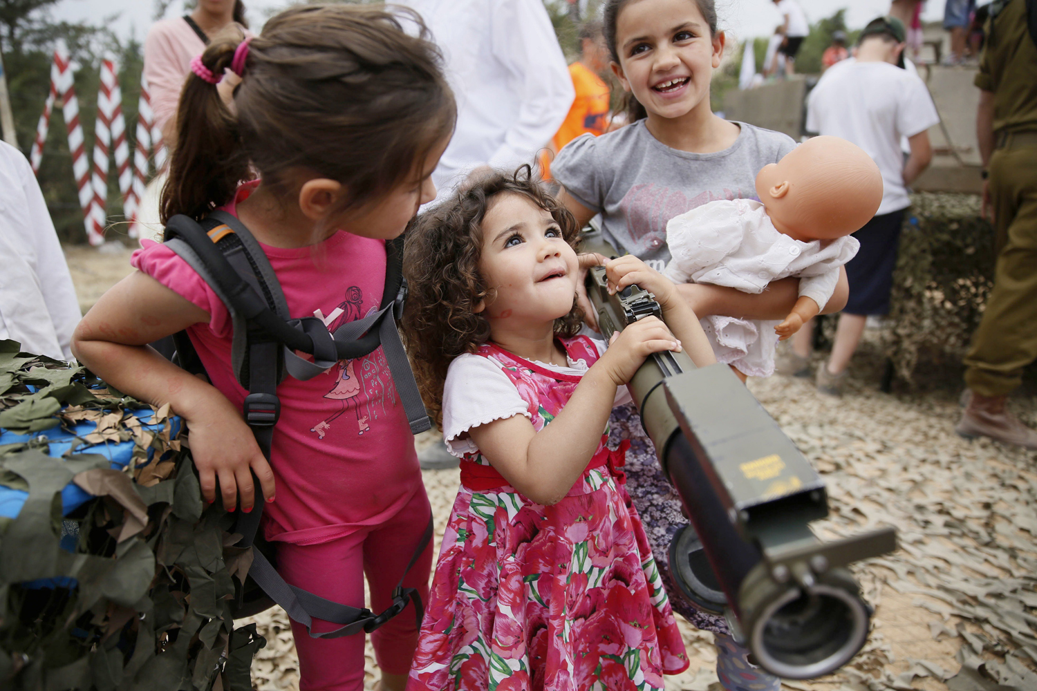 May 6, 2014. An Israeli child holds a rocket launcher as another holds her doll during a traditional military weapon display to mark the 66th anniversary of Israel's Independence at the West Bank settlement of Efrat.