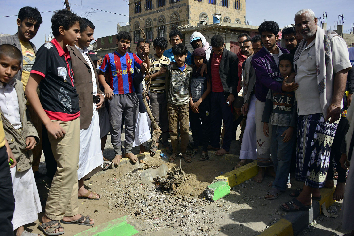 Yemenis gather at the site of a bomb explosion that targeted an army troop vehicle on its way to man a checkpoint on a street leading to two western embassies on May 9, 2014 in the capital Sanaa.