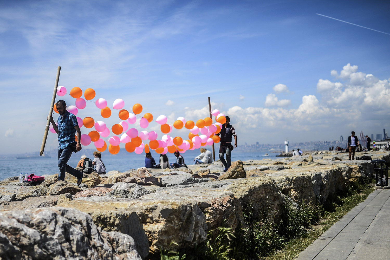 May 3, 2014. Men carry balloons near the sea at Kadikoy in Istanbul.
