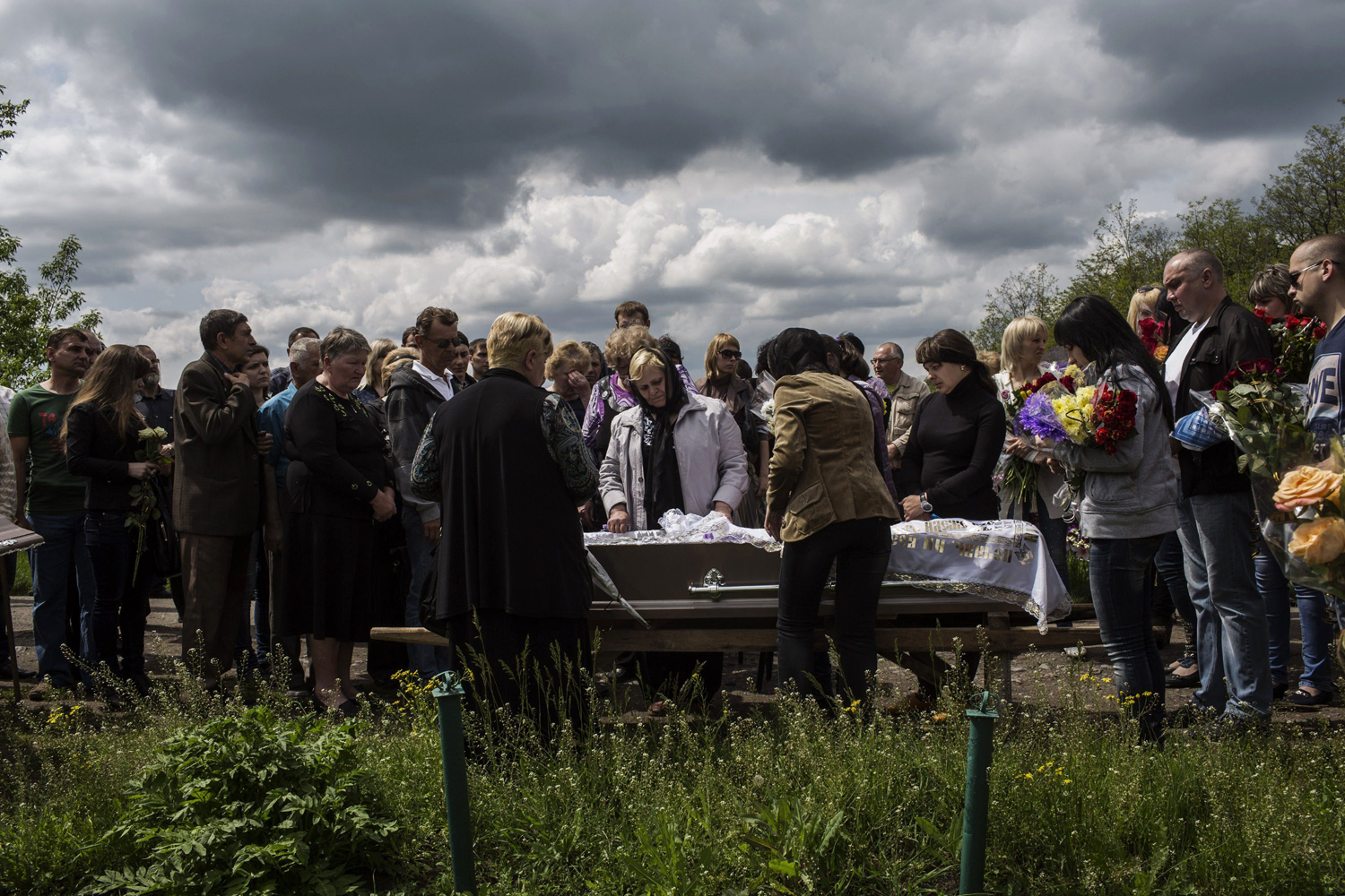 May 13, 2014. Relatives of Hyudych Vadim Yurievichq, including his mother (C), mourn his death during his funeral ceremony, at the Krasnoarmeysk cemetery, eastern Ukraine.