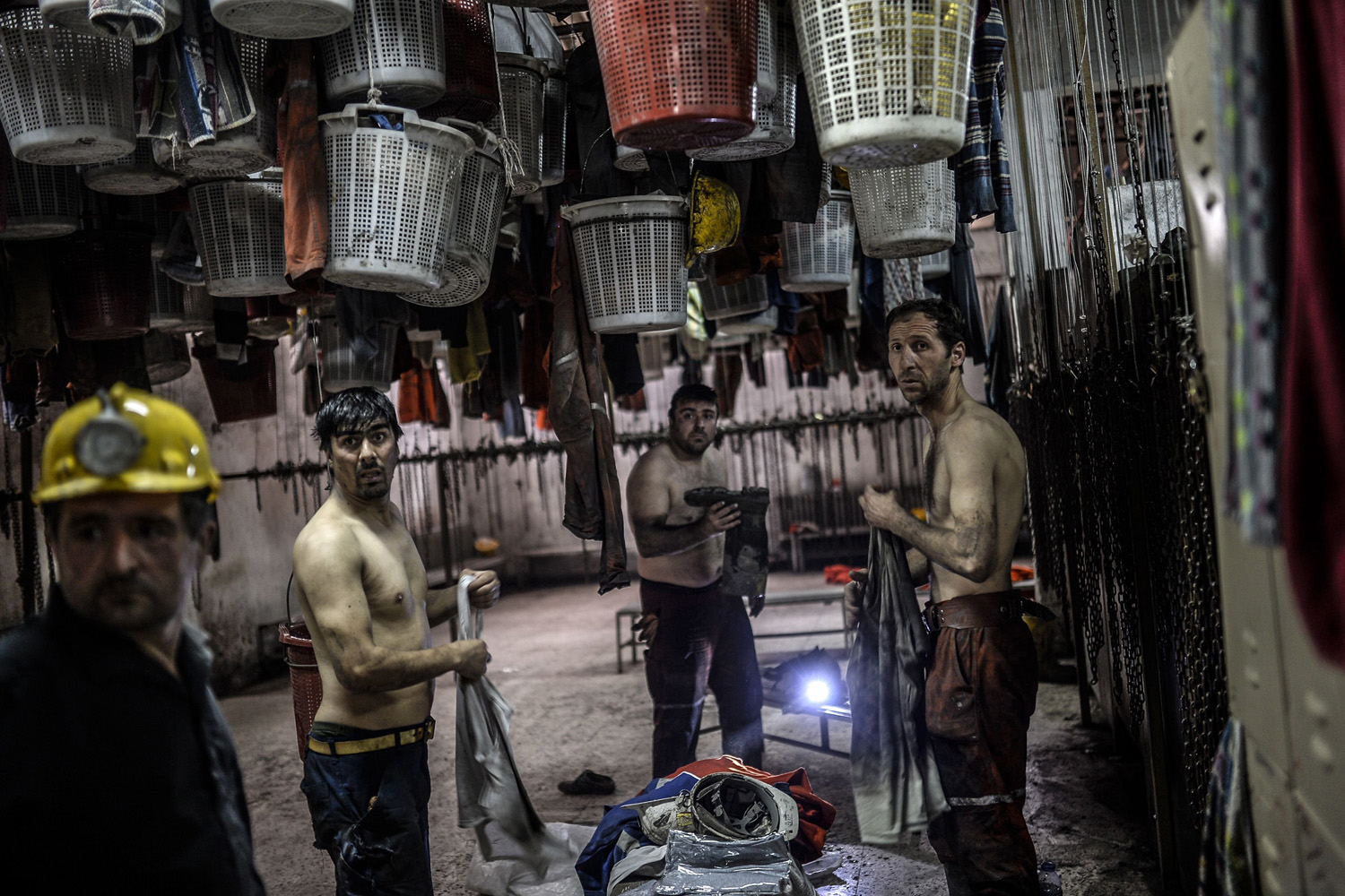 Miners change their clothes in an outside building after searching for hours for their co-workers who remain trapped undergroun in the western Turkish province of Manisa,  May 14, 2014.