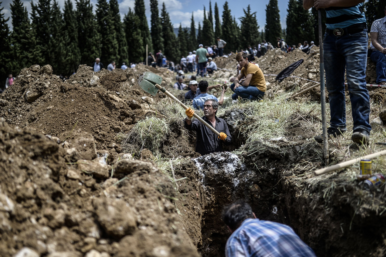 People dig graves for miners in a cemetery during the funeral ceremony of miners who died in an explosion, in the western Turkish province of  Manisa, May 15, 2014.