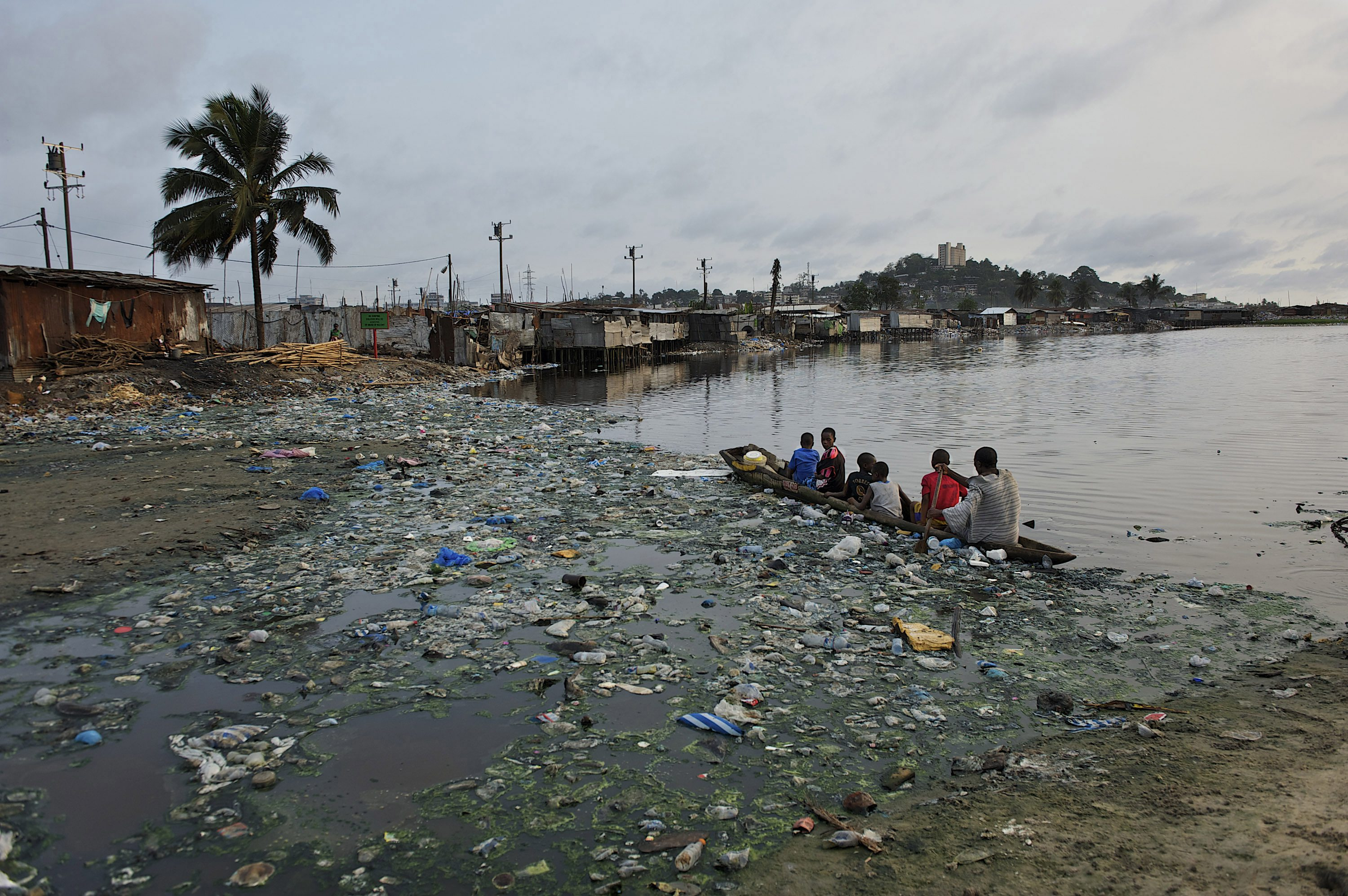 Children ride a canoe across a polluted water body near the beach at the West Point Township in Monrovia,  Liberia. The West Point Township or slum  houses over 70,000 people. Water and sanitation condition in the slum is certainly less that adequate. Due to the lack of sanitary latrines, it is common for many residents of the West Point to defecate in open near the beach.