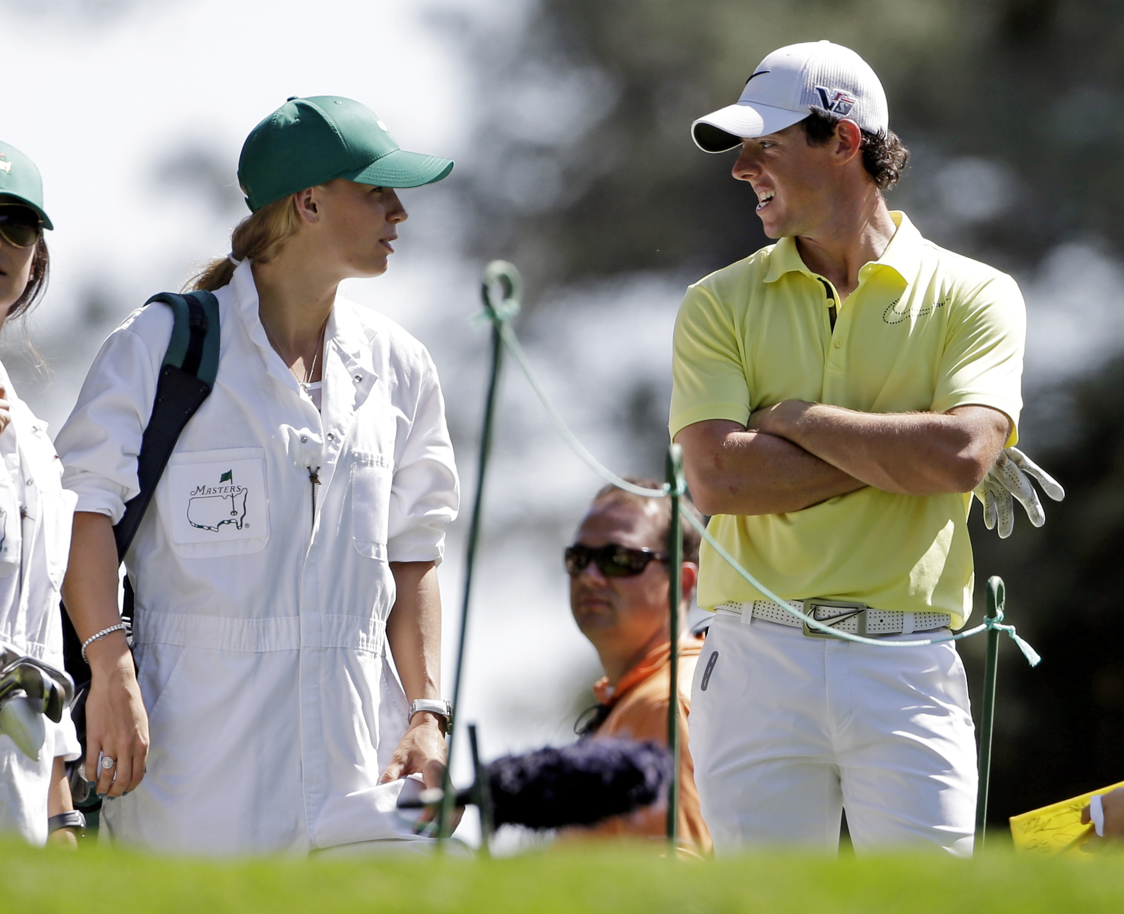 Rory McIlroy, of Northern Ireland, speaks with tennis player Caroline Wozniacki who caddied for him during the par three competition before the Masters golf tournament in Augusta, Ga. on April 10, 2013.