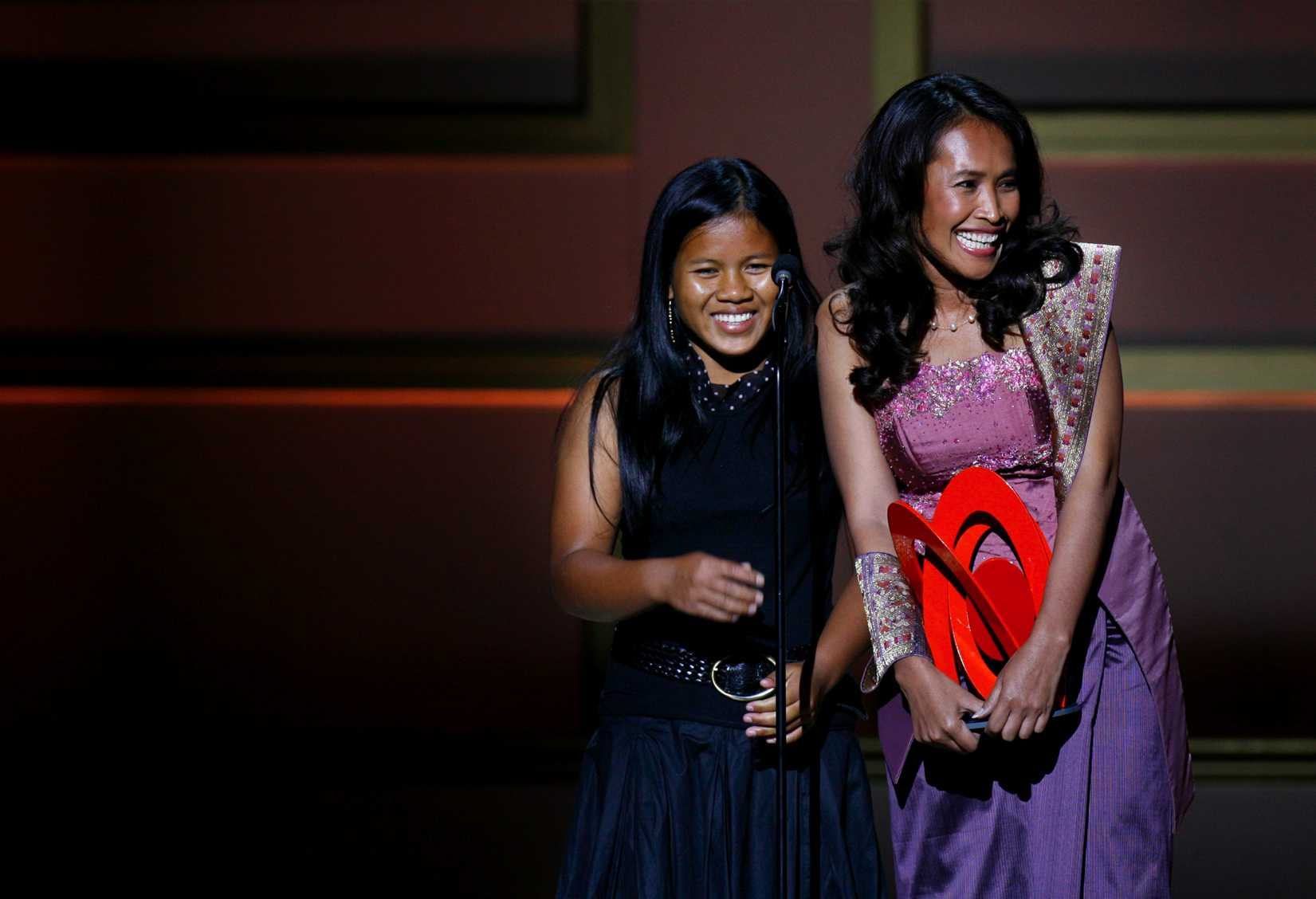 Cambodian activist Somaly Mam (R) accepts a  Woman of the Year  award with a child she rescued from sexual slavery, during the 2006 Glamour Magazine  Women of the Year  Honors award show in New York City October 30, 2006.