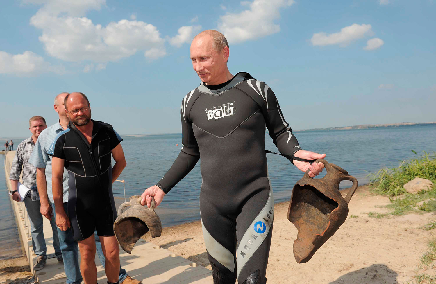 Putin carries artifacts he recovered whilst diving at an archaeological site off the Taman peninsular in southern Russia, Aug. 10, 2011.