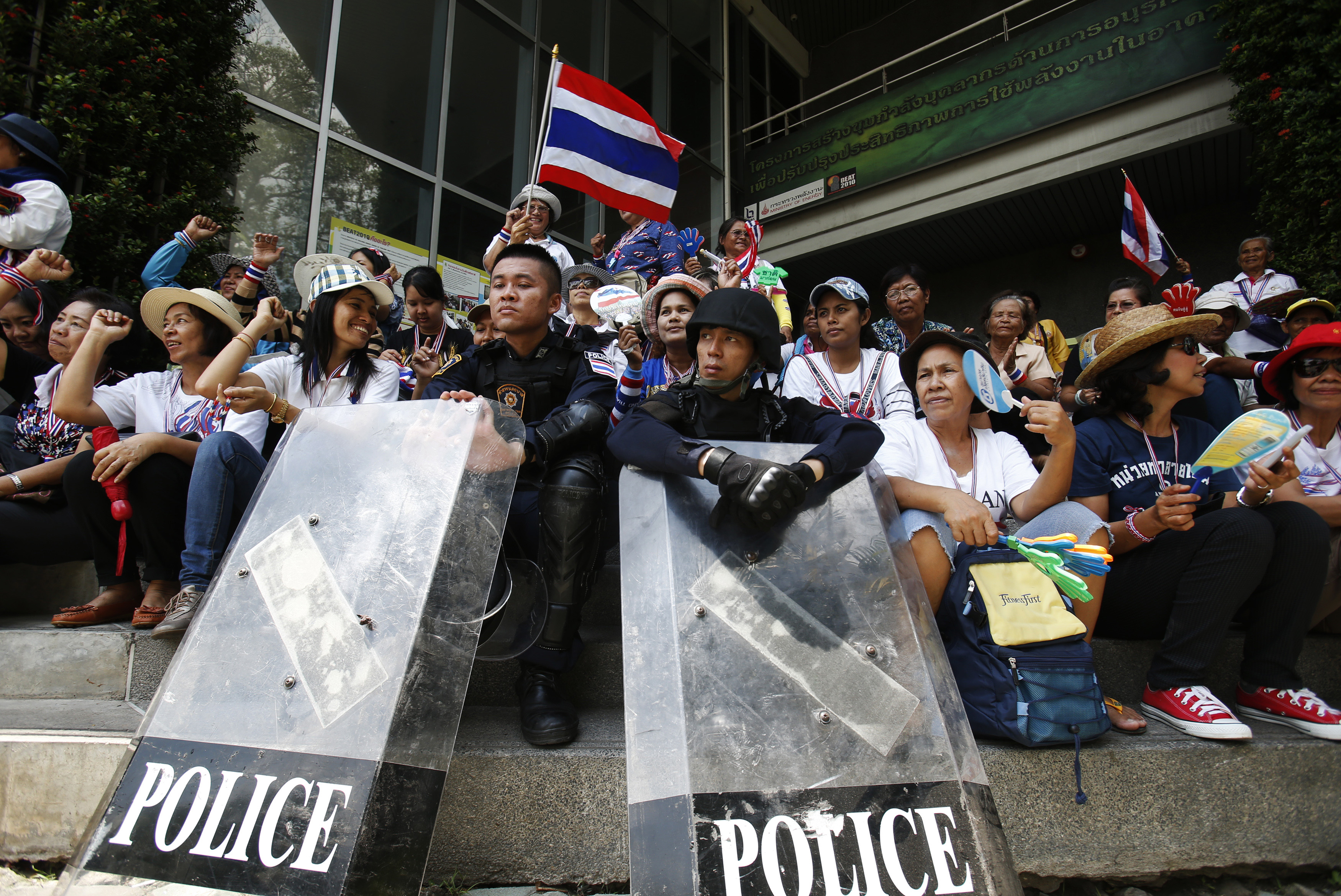 Anti-government protesters sit with riot policemen outside the National Broadcast Services of Thailand (NBT) television station in Bangkok May 9, 2014.