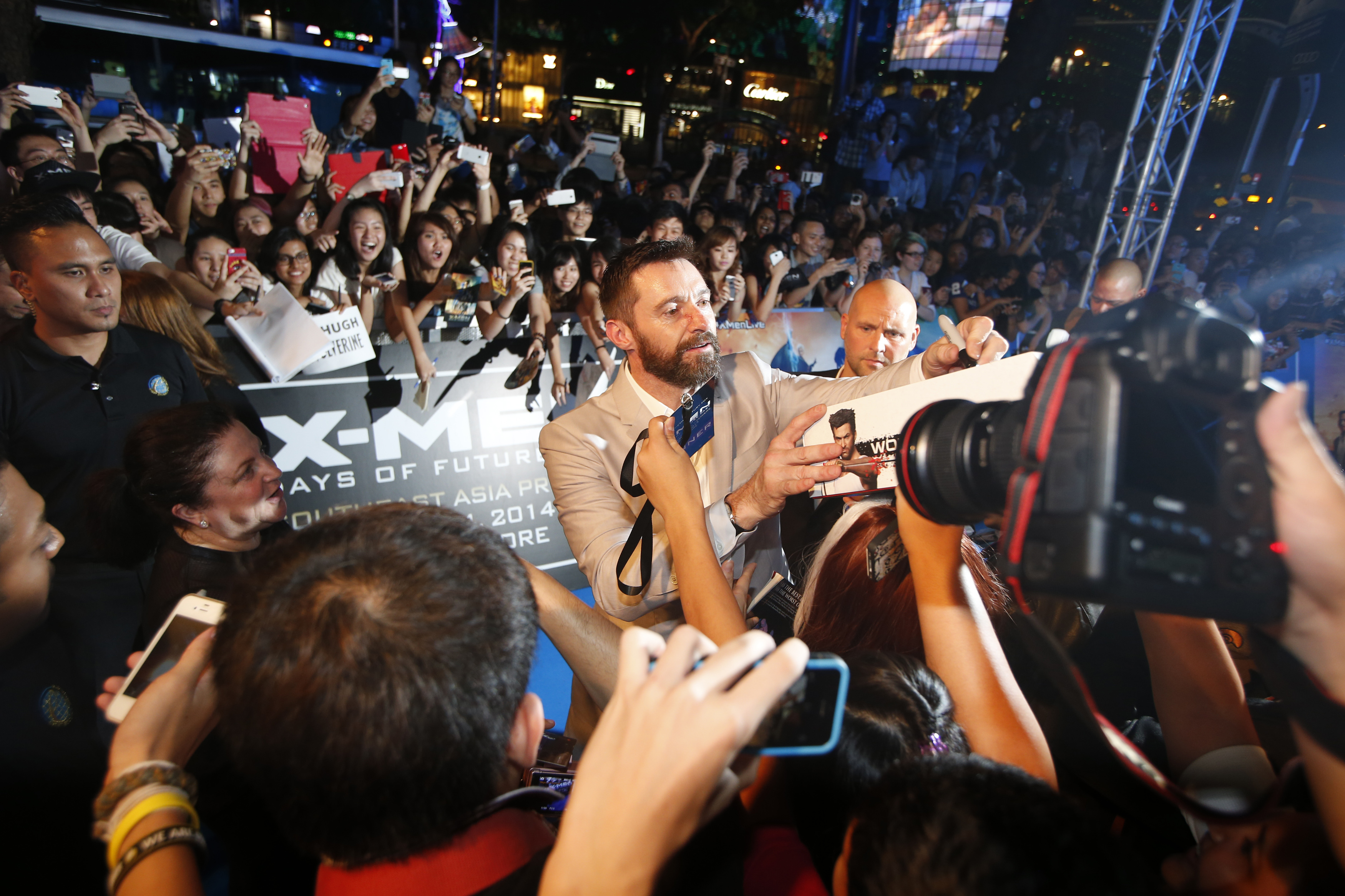 Cast member Hugh Jackman signs autographs for fans at the Southeast Asia premiere of X-Men: Days of Future Past in Singapore on May 14, 2014