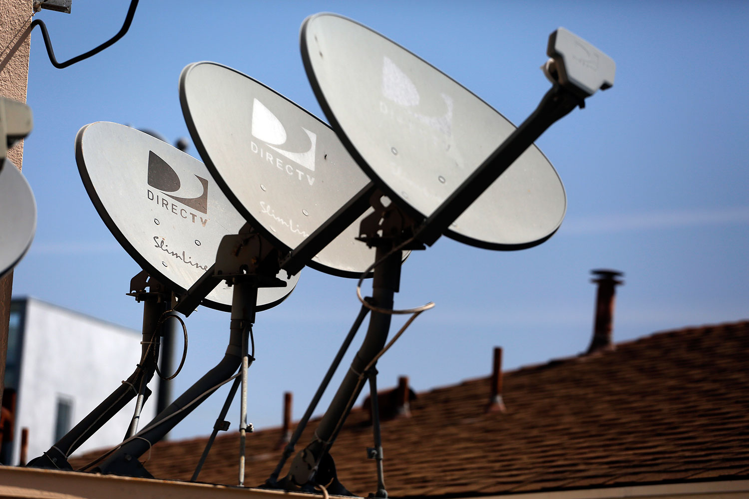 DirecTV satellite dishes are seen on an apartment roof in Los Angeles, May 18, 2014.