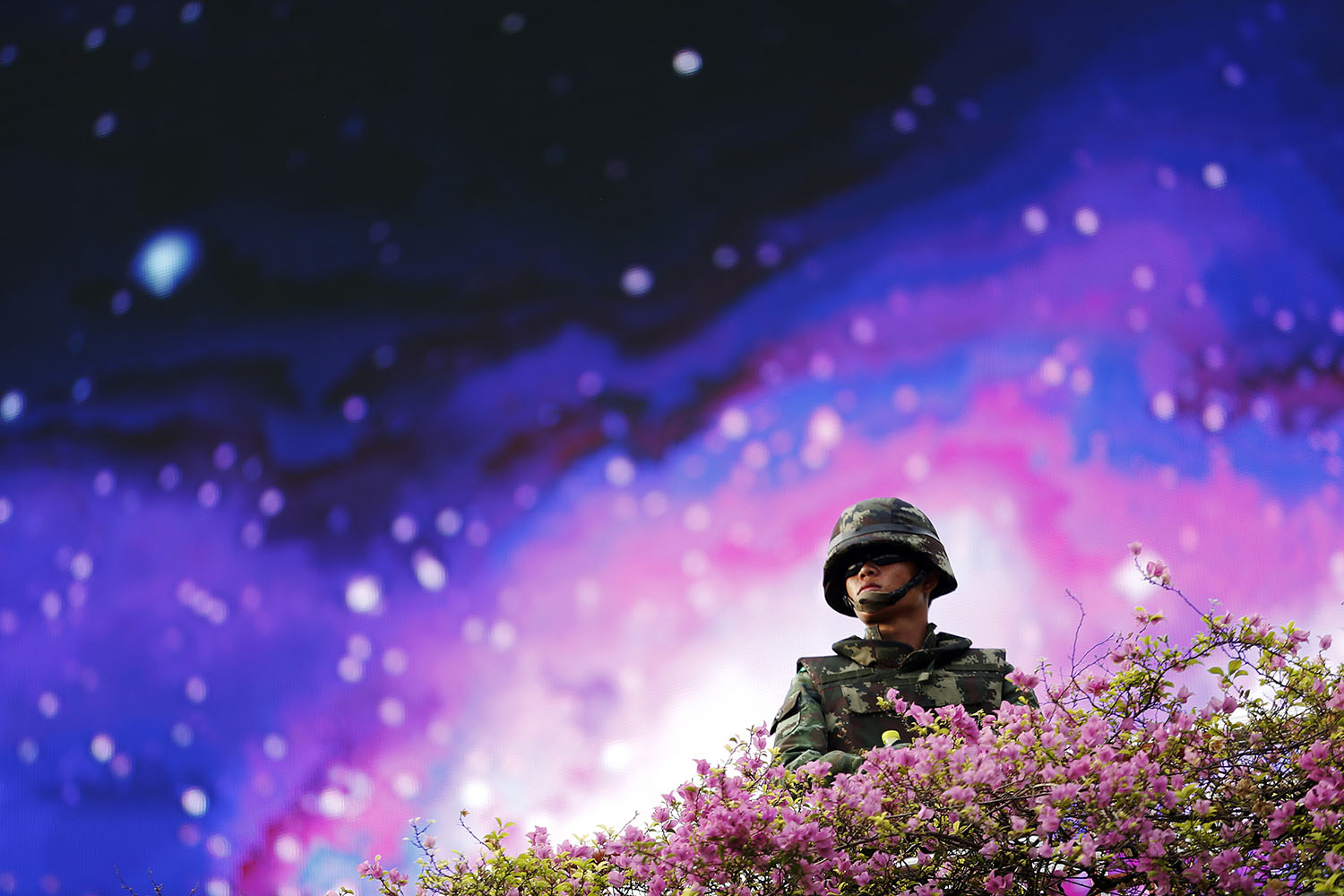 May 30, 2014. A soldier takes up position in front of a large screen at the Victory Monument in Bangkok Thailand, where anti-coup protesters had gathered on previous days to rally against the military coup.