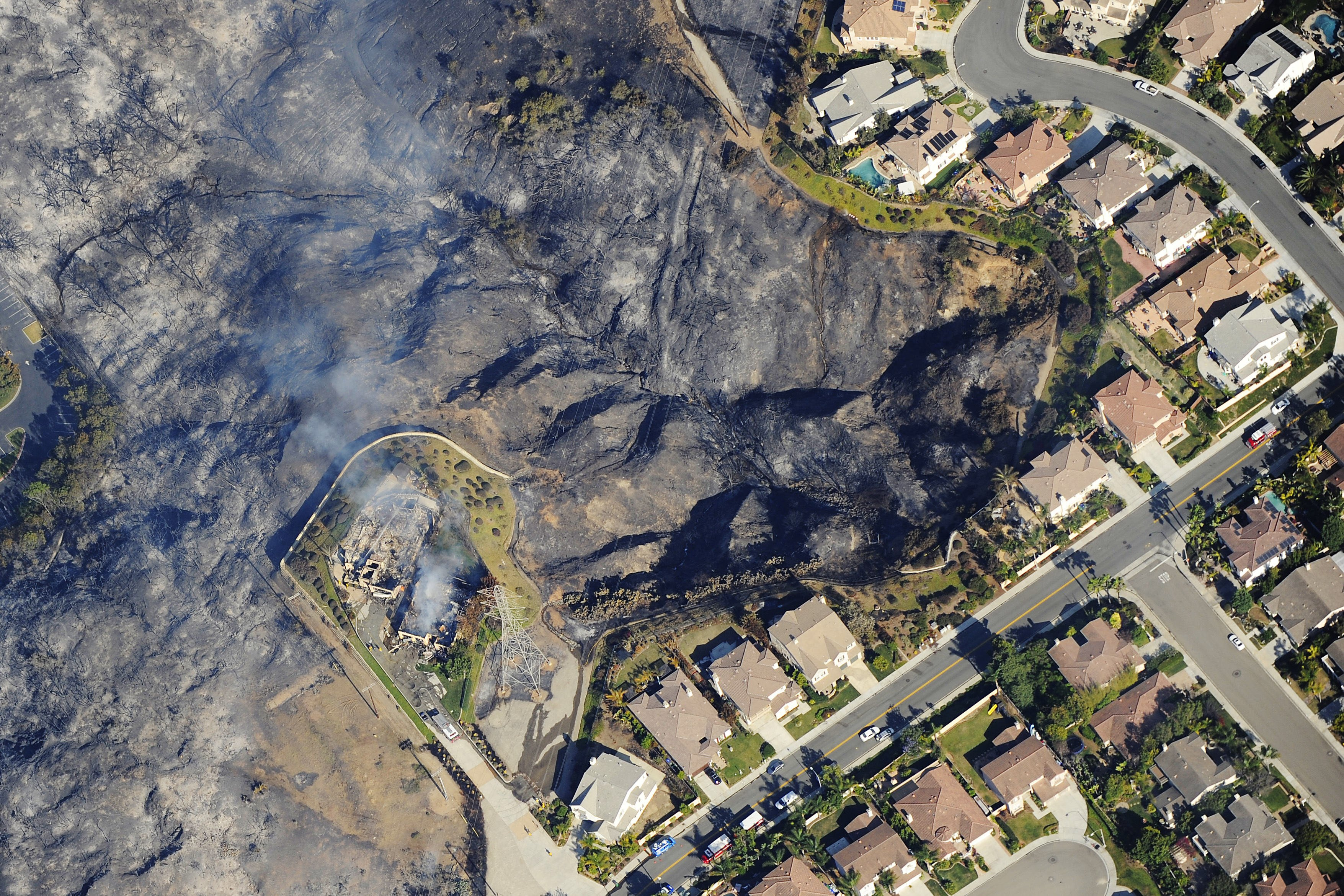 Houses smolder after a wildfire destroyed them, Carlsbad, Calif., May 14, 2014.