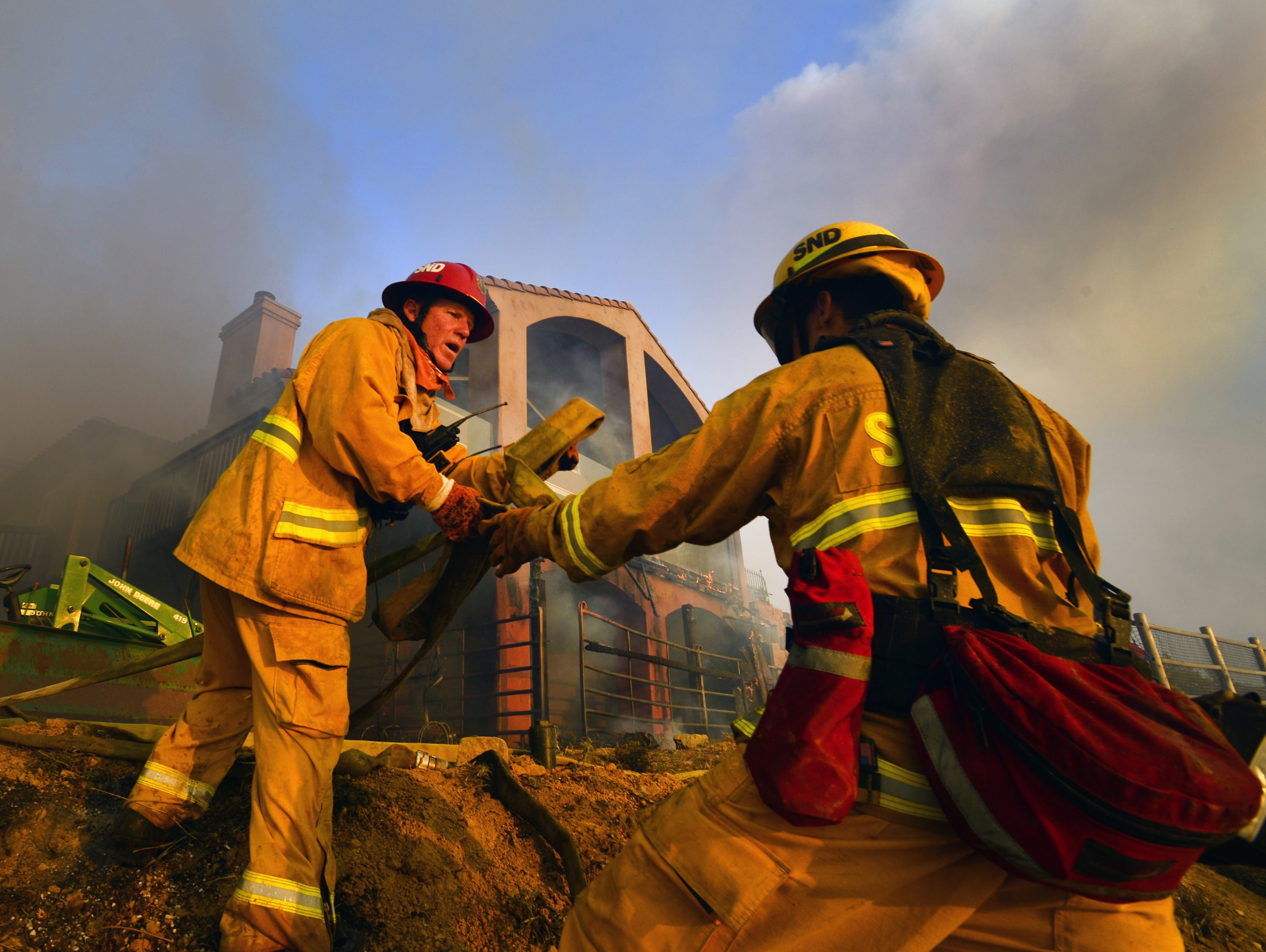 Firefighters work to set up a hose as the porch of a home burns in San Marcos, in the San Diego county on May 14, 2014.