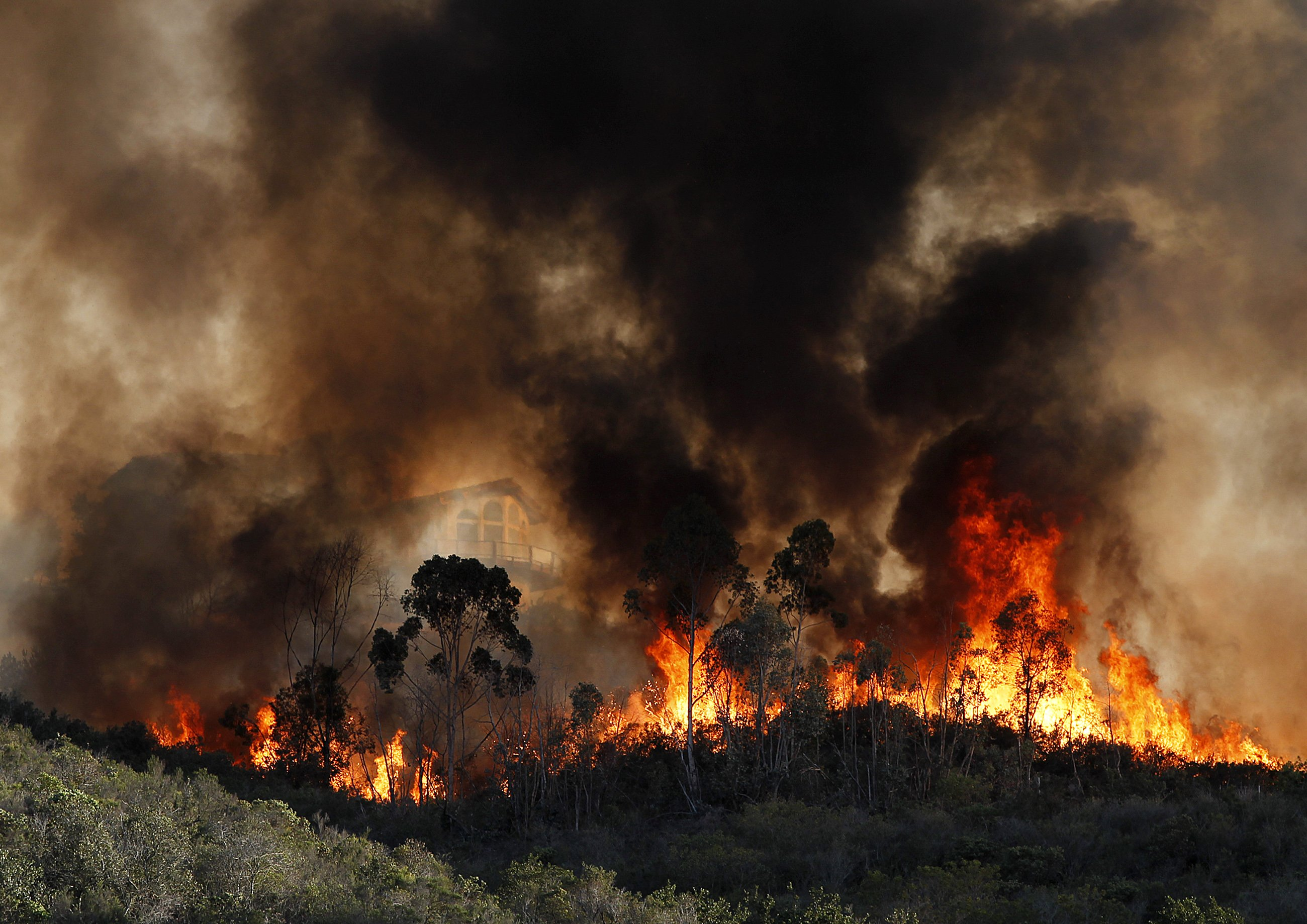 Flames surround a large Coronado Hills neighborhood hill-top home that started to catch fire near Cal State San Marcos as crews battle a large wildfire threatening homes on May 14, 2014 in San Diego.