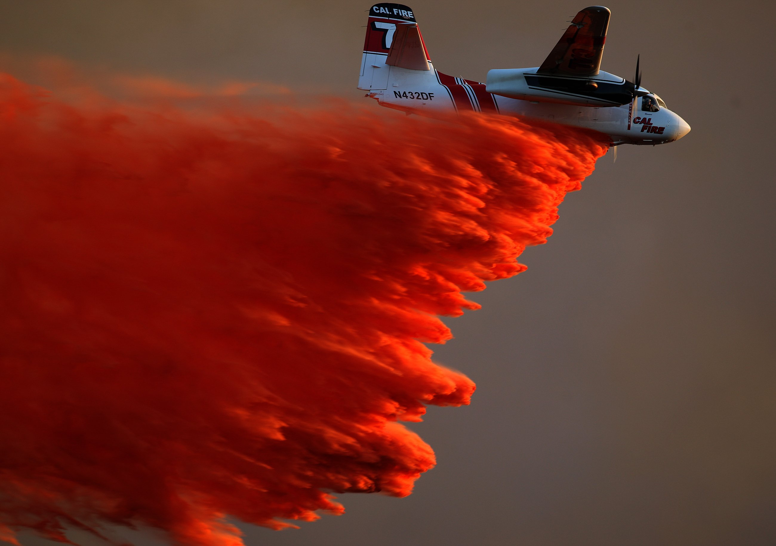 A Cal Fire airplane drops fire retardant on brush near Cal State San Marcos as crews battle a large wildfire threatening homes on May 14, 2014 in San Diego.