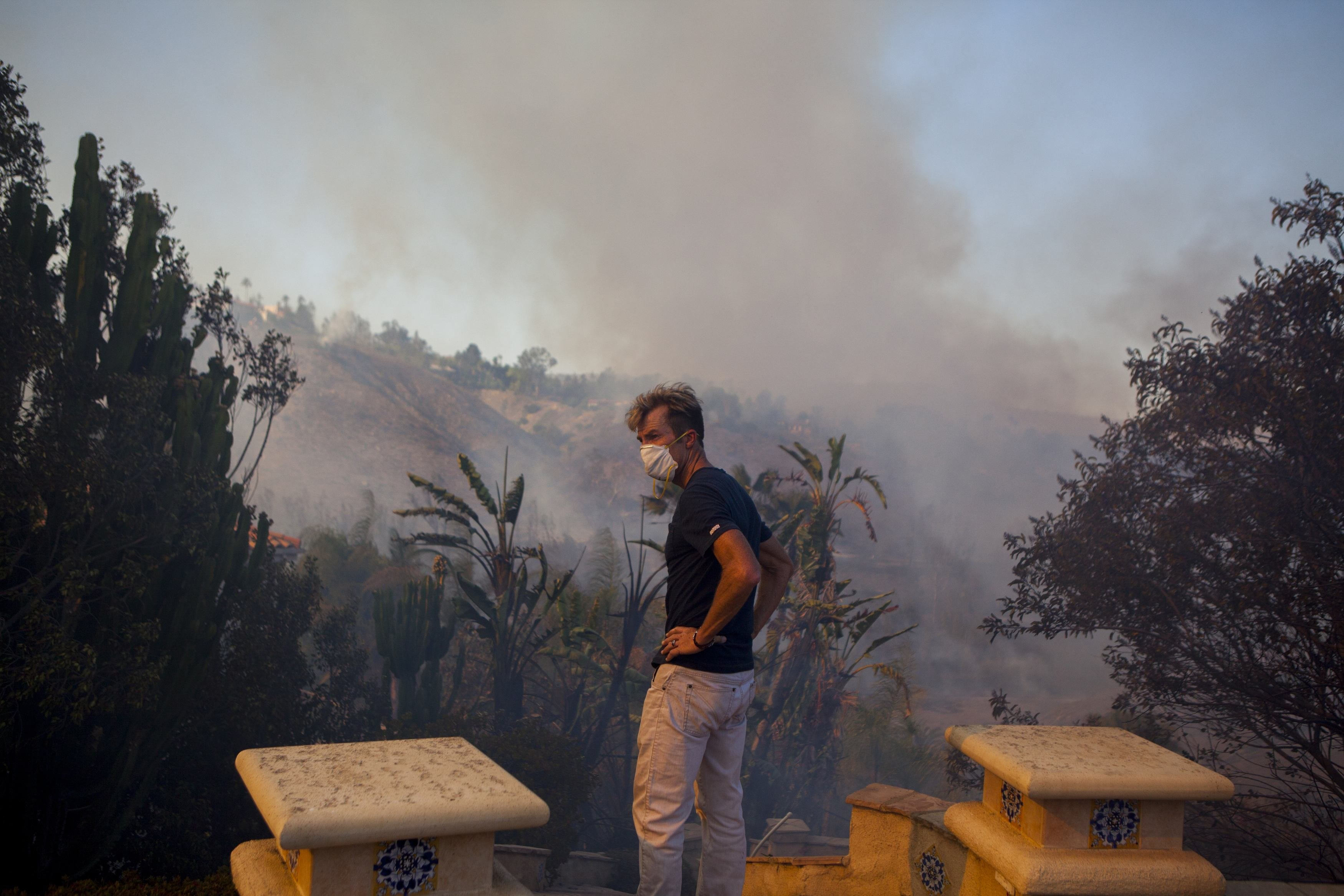 Jonathon Collopy, a resident of Fairbanks Ranch neighborhood, watches the fire burn near his house outside San Diego on May 13, 2014.