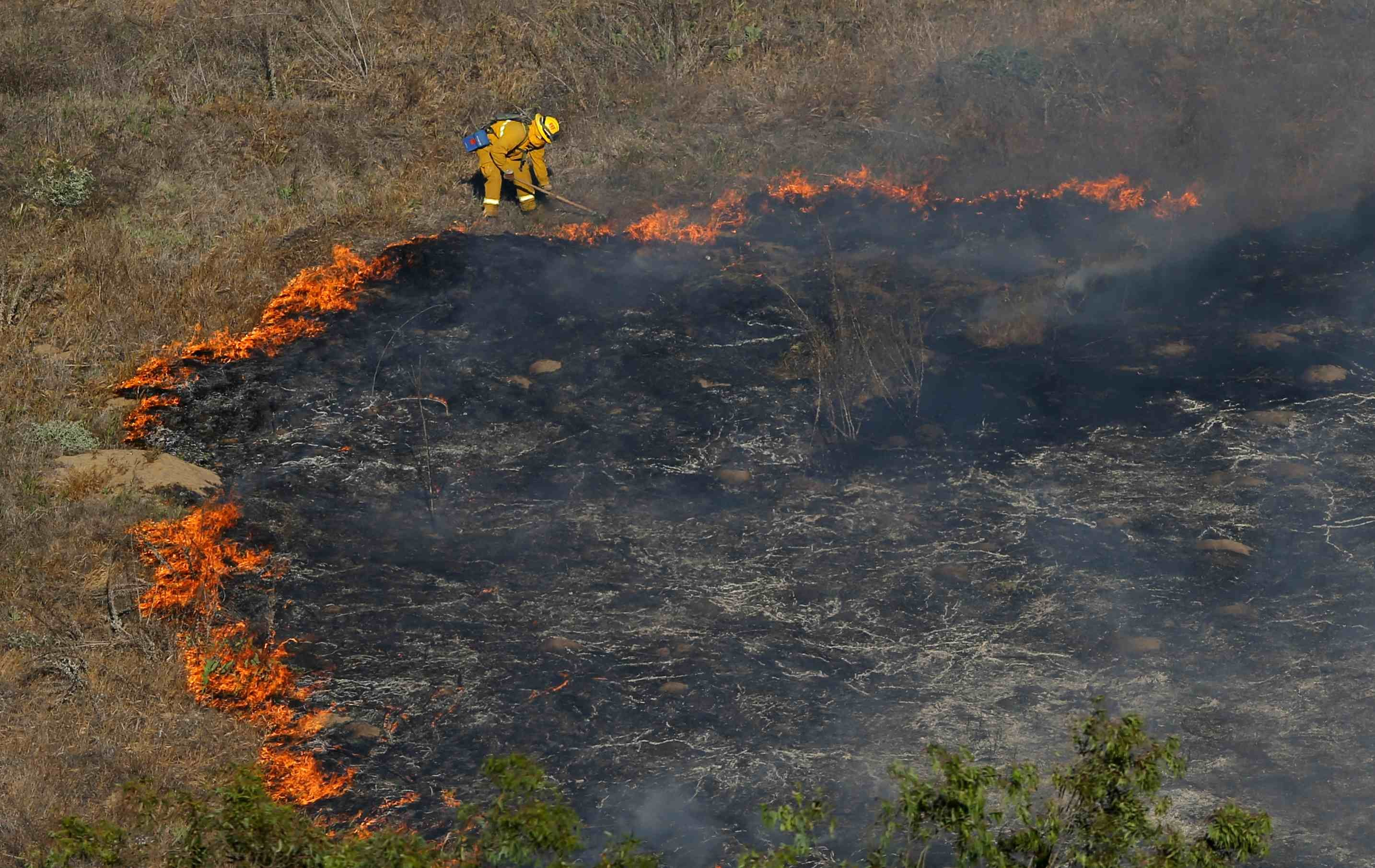 A firefighter works in a canyon to help extinguish the fire north of San Diego on May 13, 2014.