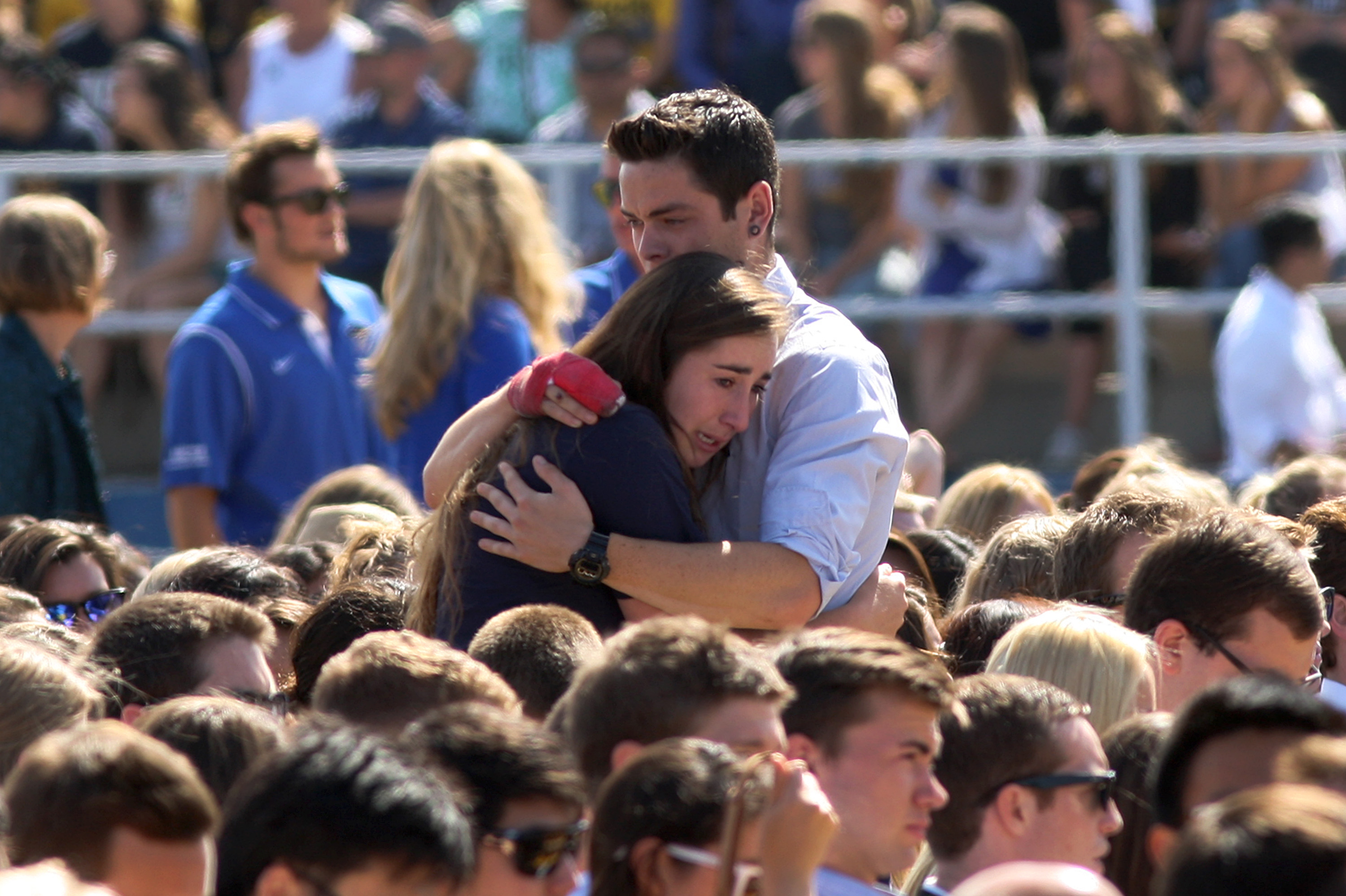 People hug at a public memorial on the Day of Mourning and Reflection for the victims of a killing spree at University of California, Santa Barbara on May 27, 2014 in Isla Vista, California.