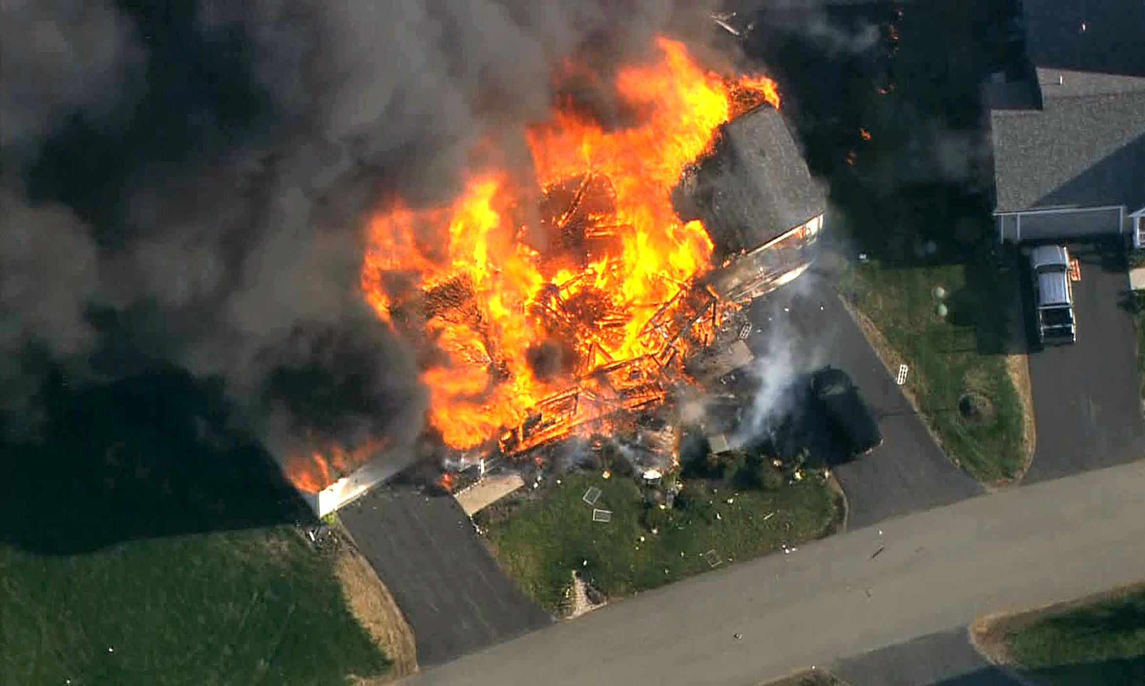In this frame grab from television helicopter video, a home bursts into flames in Brentwood, N.H.