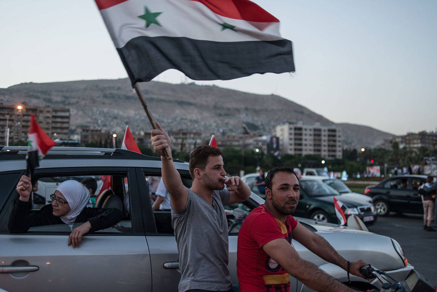 Syrian supporters of presidential candidate Bashar al-Assad wave Syrian national flags during a rally in Damascus, Syria, on May 30, 2014.