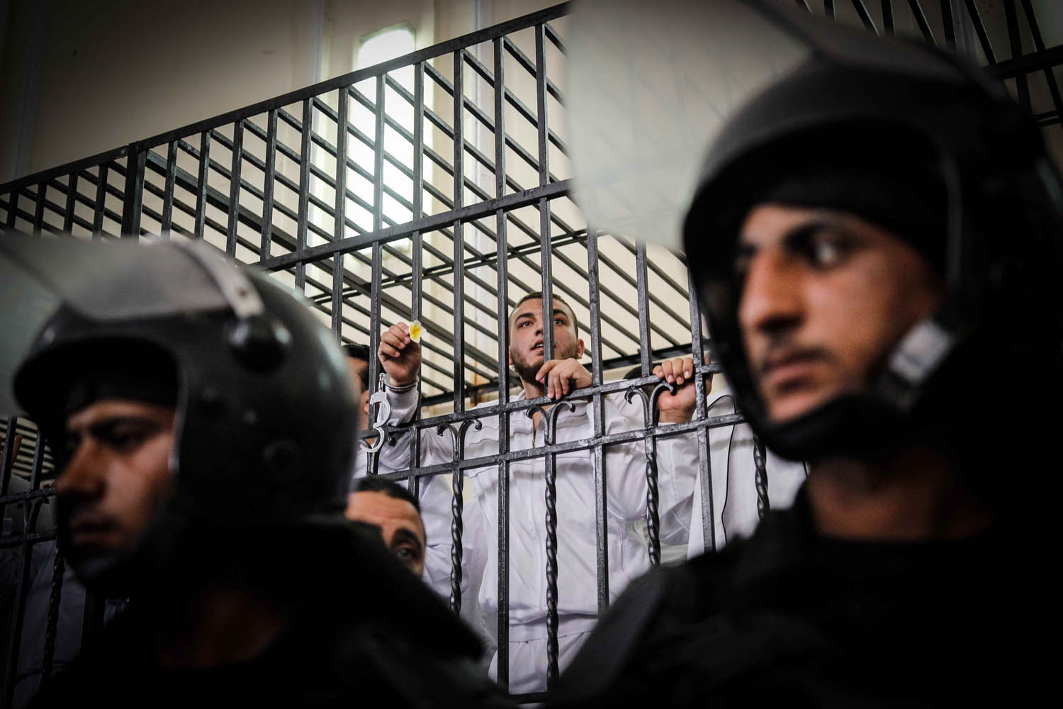 May 19, 2014. Egyptian defendants react in a cage on a court of their trial over violence during 2013 clashes in the Sidi Gaber neighborhood of Alexandria, Egypt.