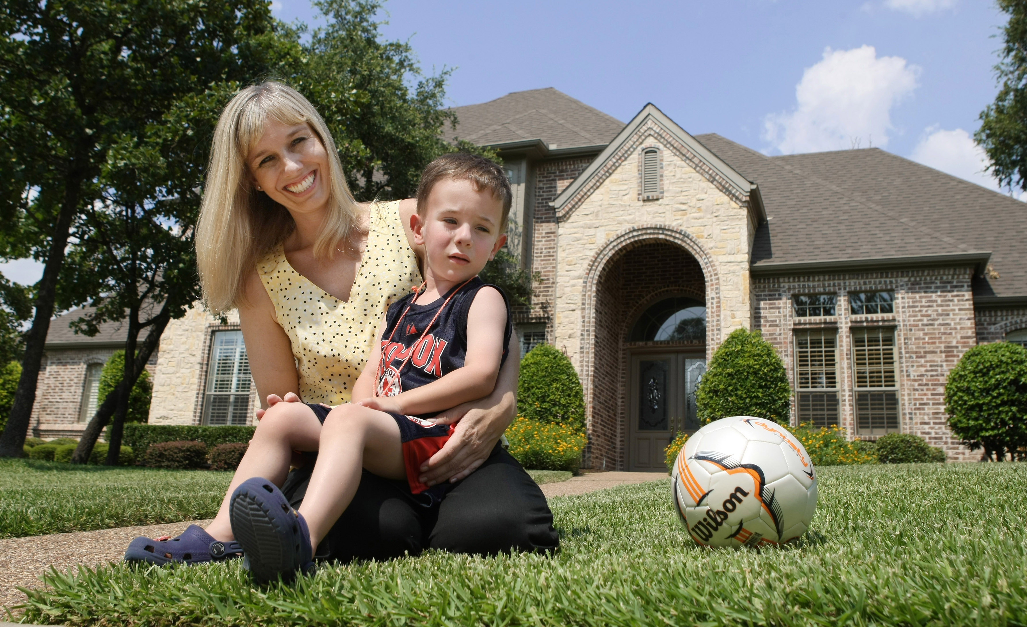 Kelly McGuire Lynch poses at her soon-to-be ex-home in Southlake, Texas, with her son Patrick, June 24, 2009.