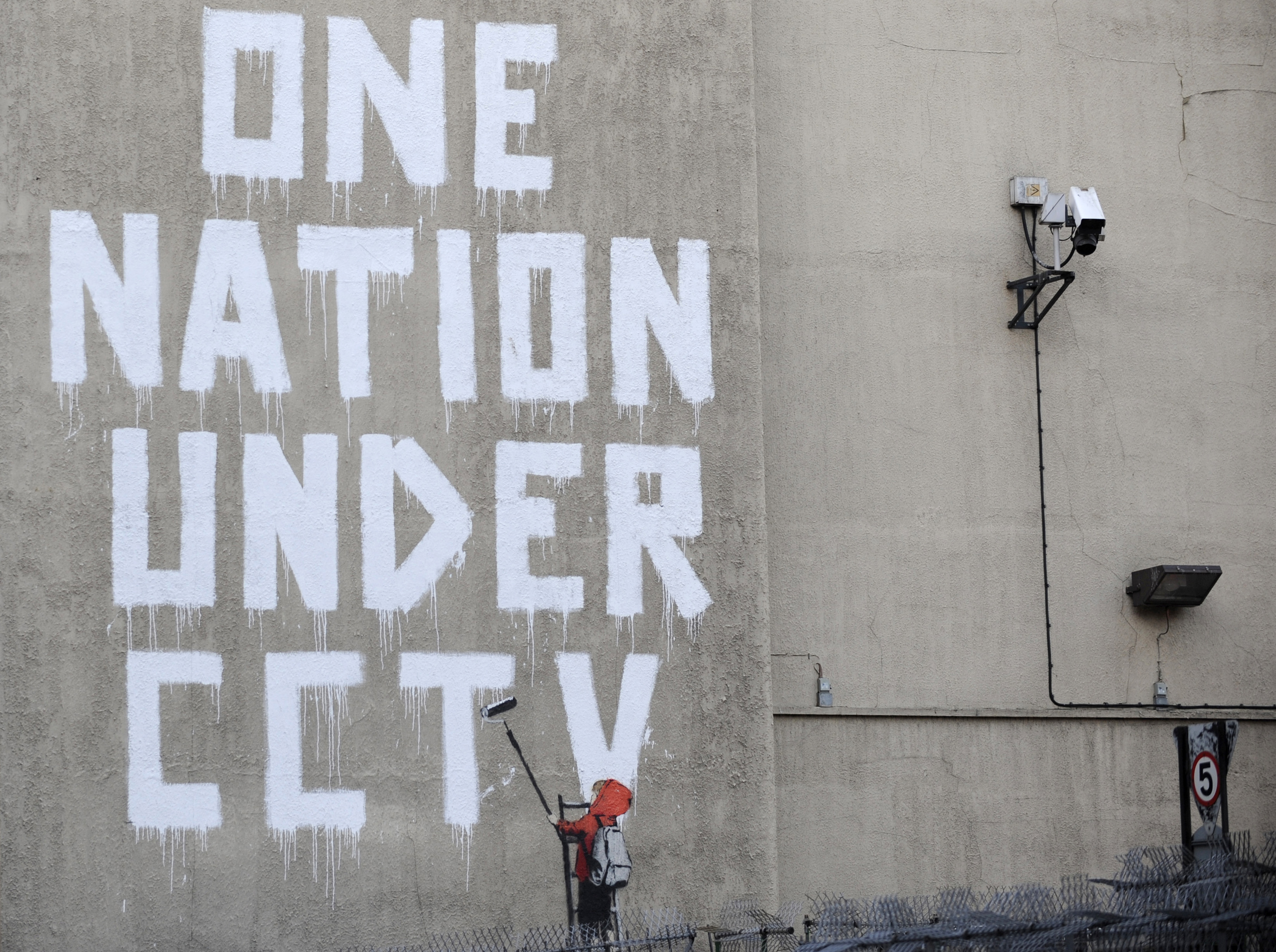 Street graffiti by elusive graffiti artist Banksy is seen on a wall, next to a CCTV camera, in central London on Nov. 25, 2008.