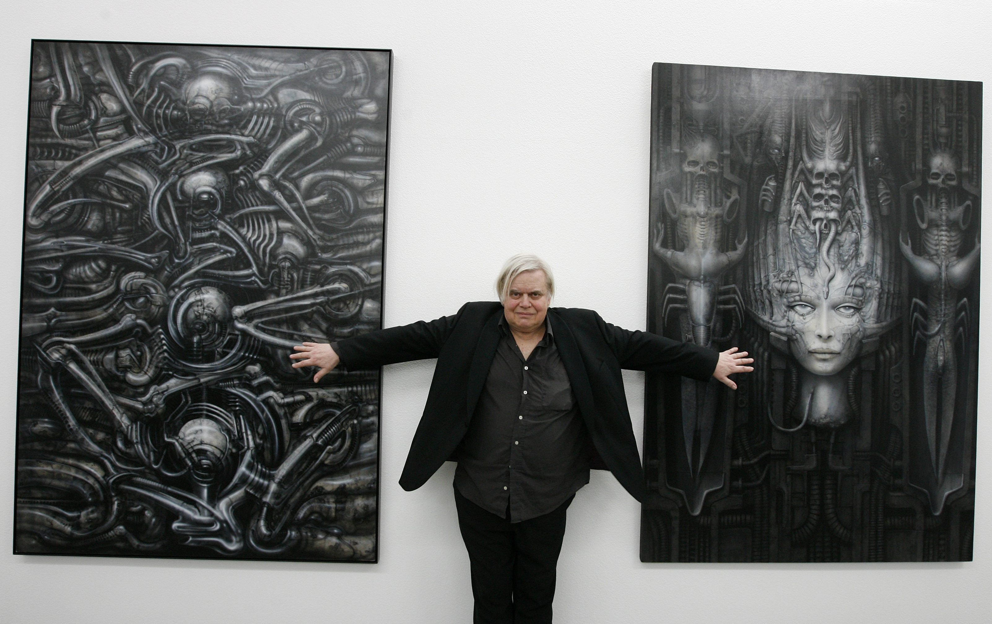 Swiss artist H.R. Giger poses with two of his works at the art museum in Chur, Switzerland.