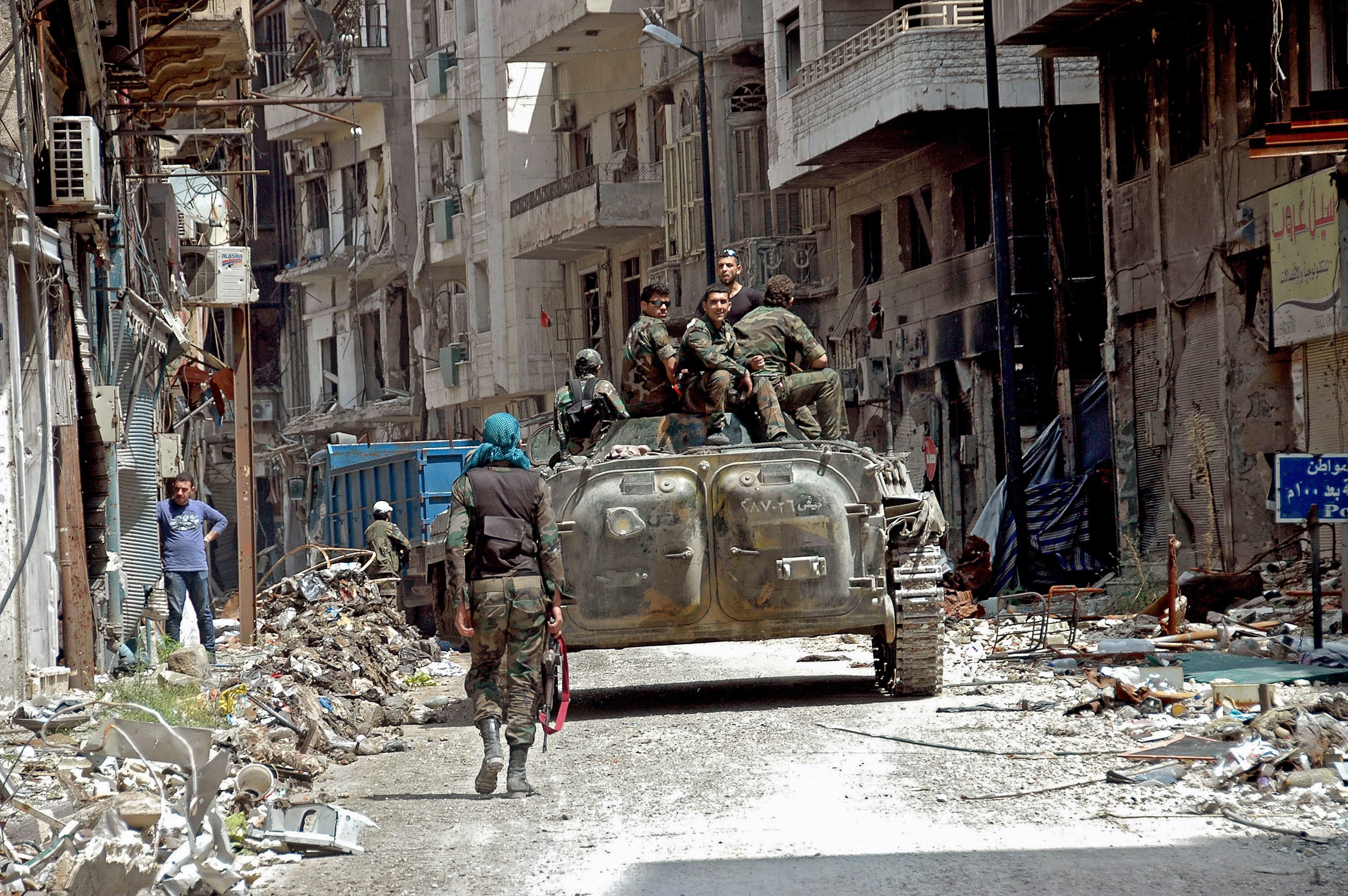 Syrian army sit on their armored vehicles while patrolling streets in Homs, Syria, May 9, 2014.