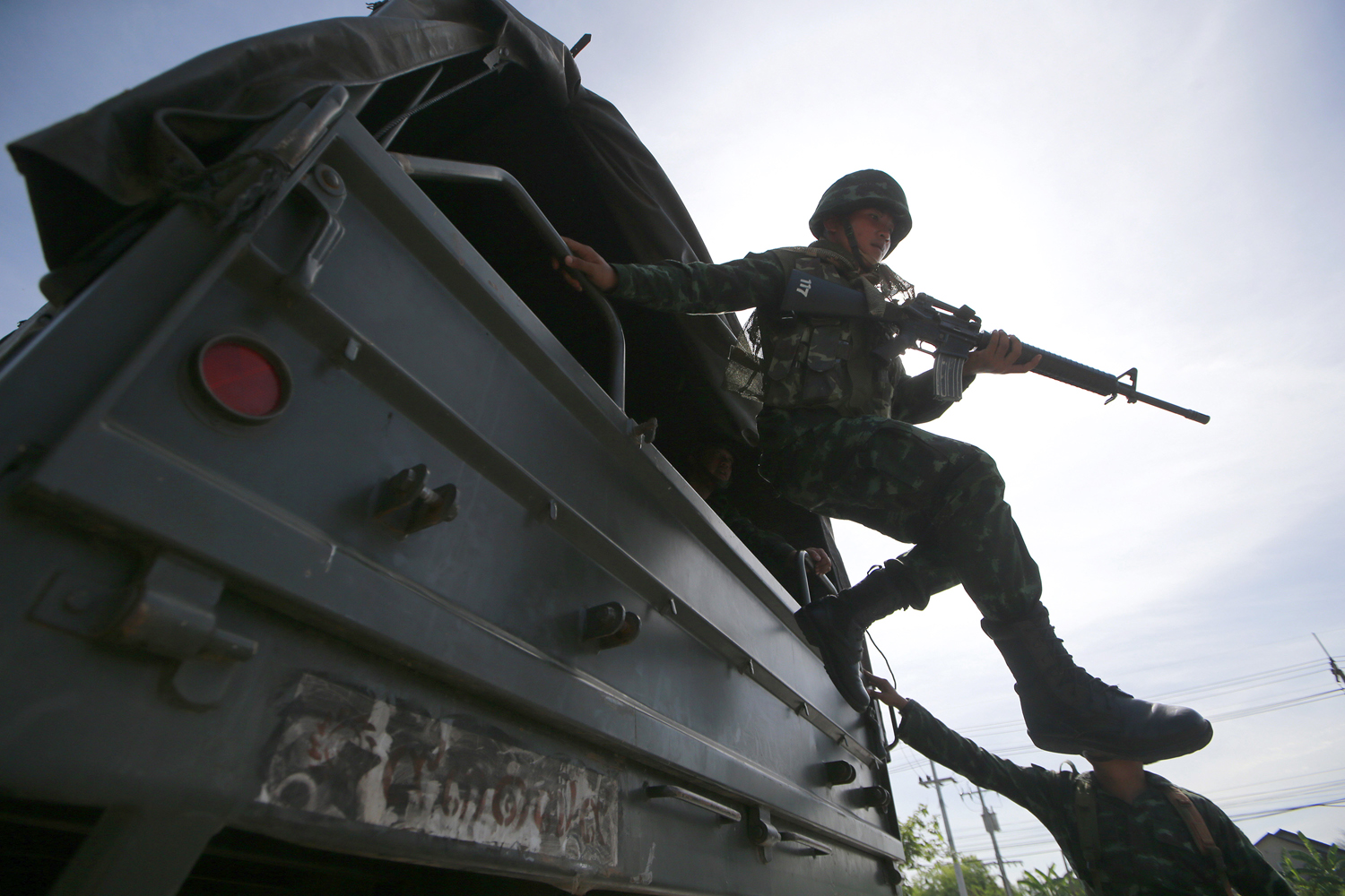 A Thai soldier jumps off a military truck after arriving at a progovernment rally site on the outskirts of Bangkok on Tuesday, May 20, 2014.