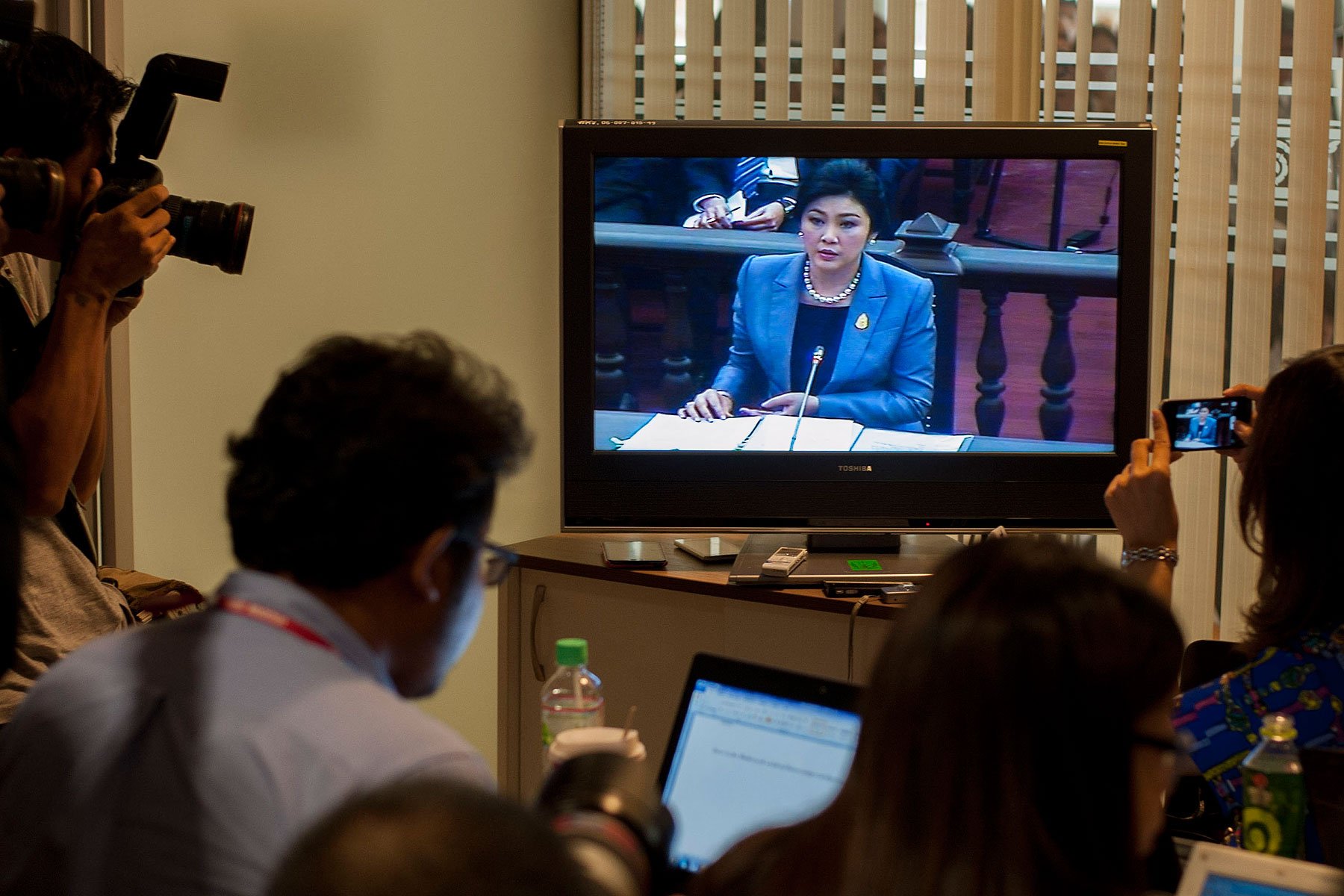Thai Prime Minister Yingluck Shinawatra is seen on a TV during her statement at the Constitutional Court on May 6, 2014, in Bangkok