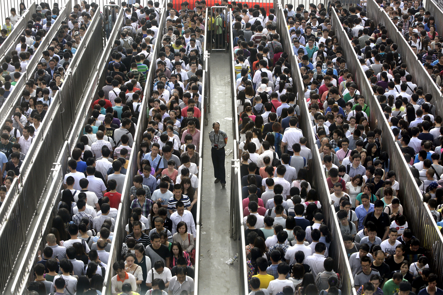 A security officer stands guard as passengers line up and wait for a security check during morning rush hour at Tiantongyuan North Station in Beijing on May 27, 2014