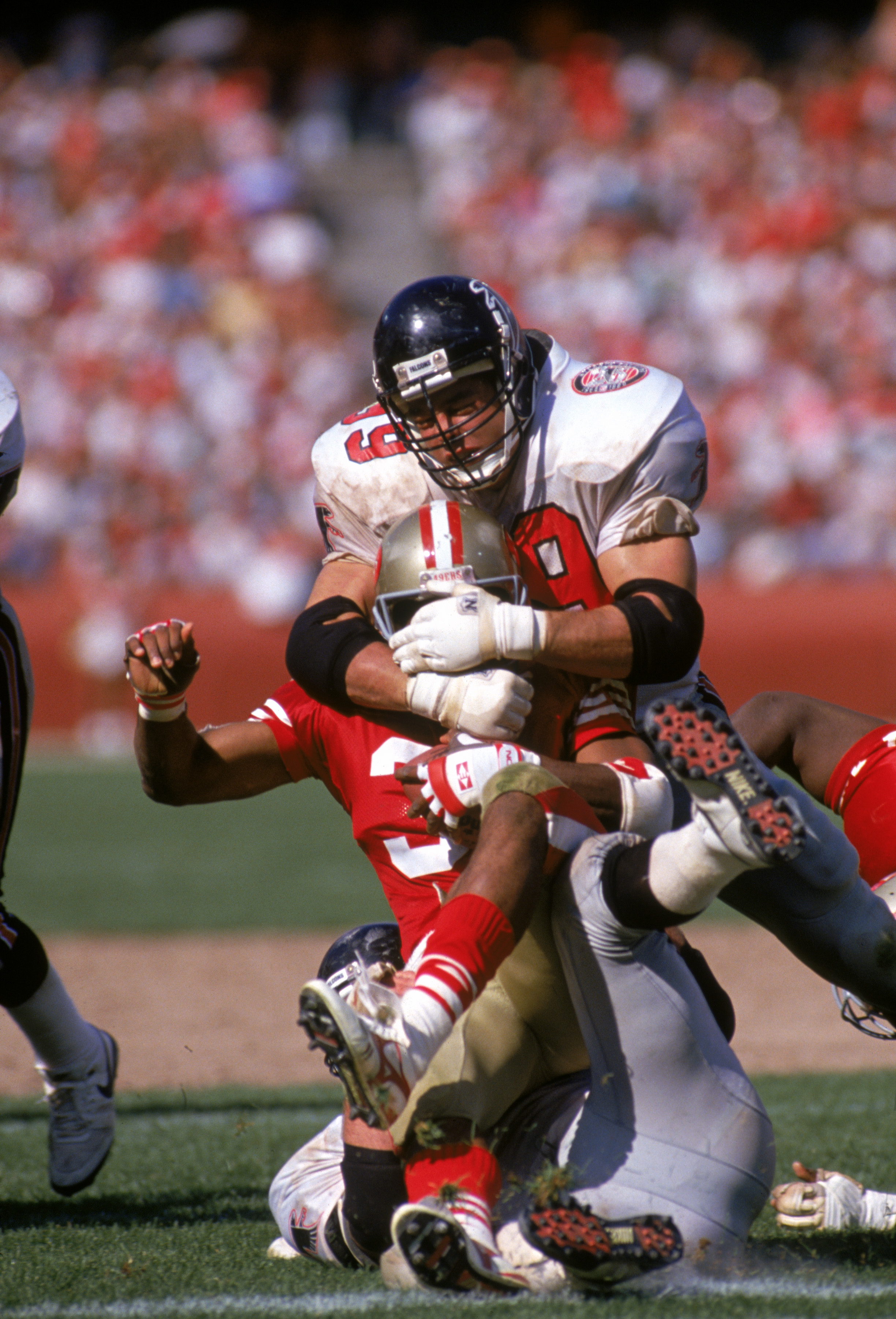 Defensive end Tim Green #99 of the Atlanta Falcons tackles running back Roger Craig #33 of the San Francisco 49ers during a game at Candlestick Park on Sept. 23, 1990 in San Francisco.