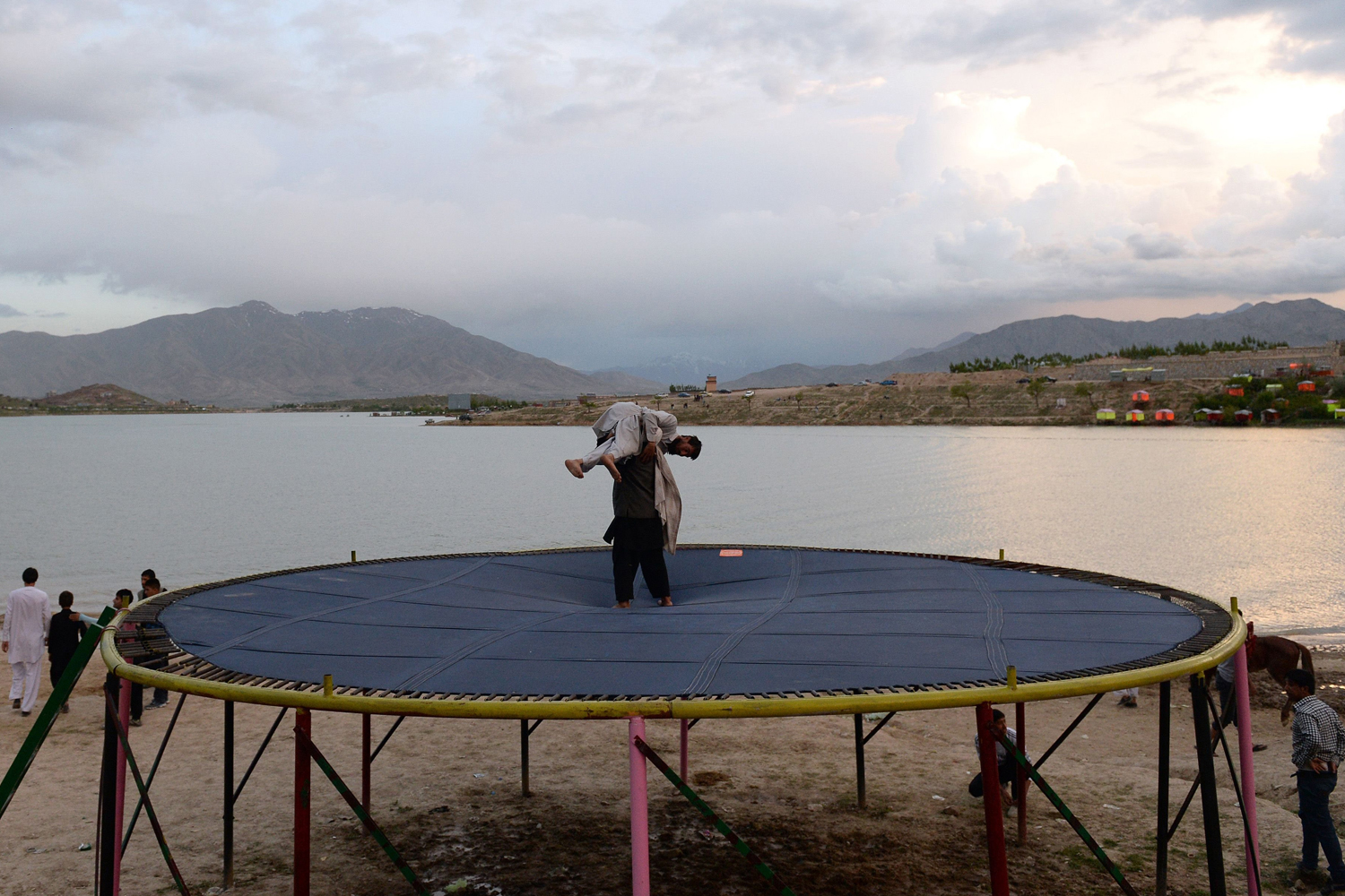 May 9, 2014. Afghan youths wrestle on a trampoline on the banks of Qargha Lake in the outskirts of Kabul.